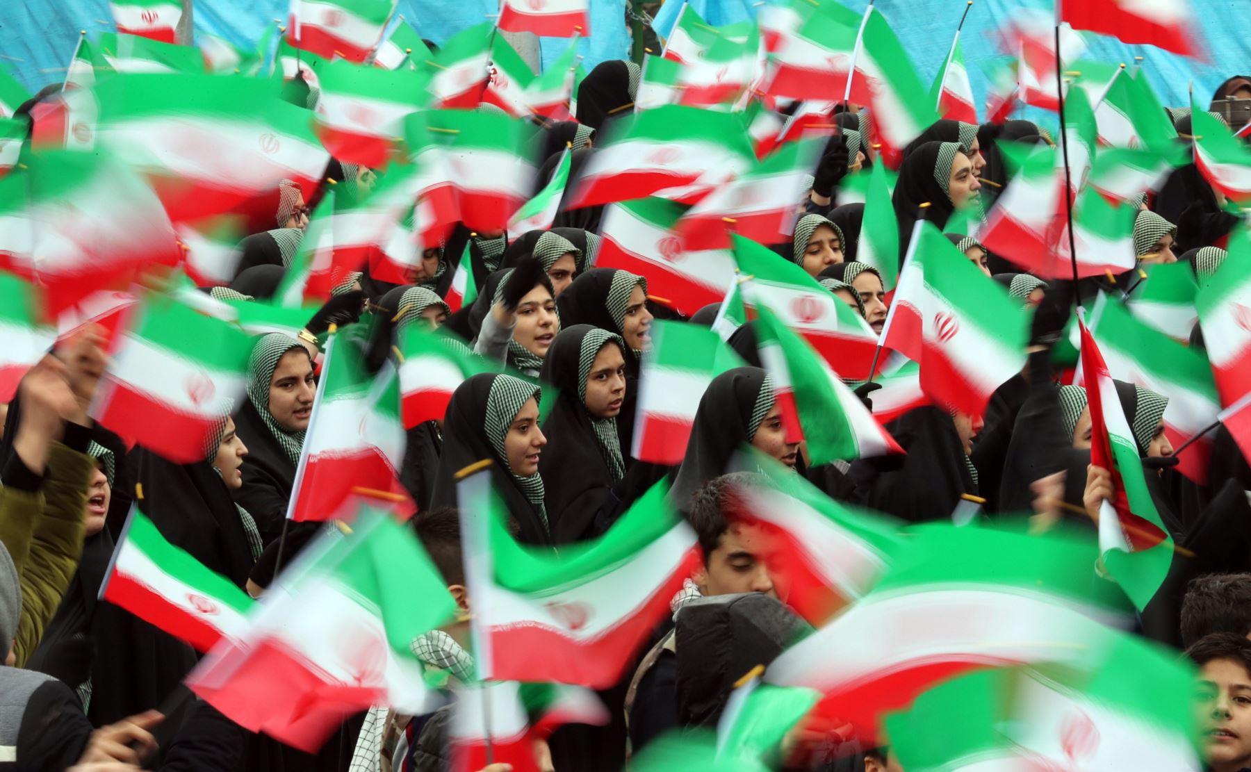 Varias estudiantes ondean banderas iraníes durante una ceremonia por el 40º aniversario de la Revolución Islámica de 1979 este lunes en la plaza Azadi (Libertad) de Teherán (Irán). EFE/ Abedin Taherkenareh