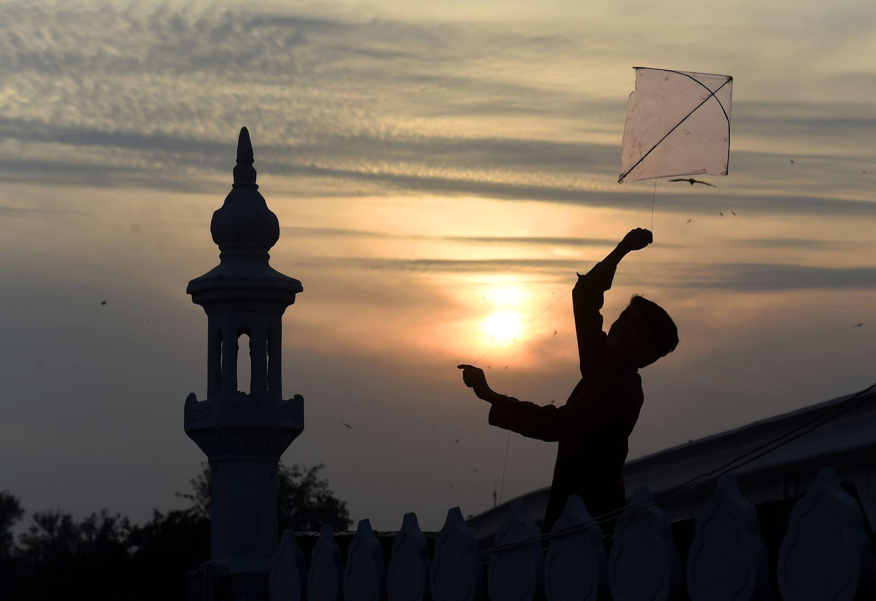 Un niño pakistaní vuela una cometa en el techo de una mezquita durante la puesta de sol en Lahore el 11 de febrero de 2019. Foto: AFP/ARIF ALI