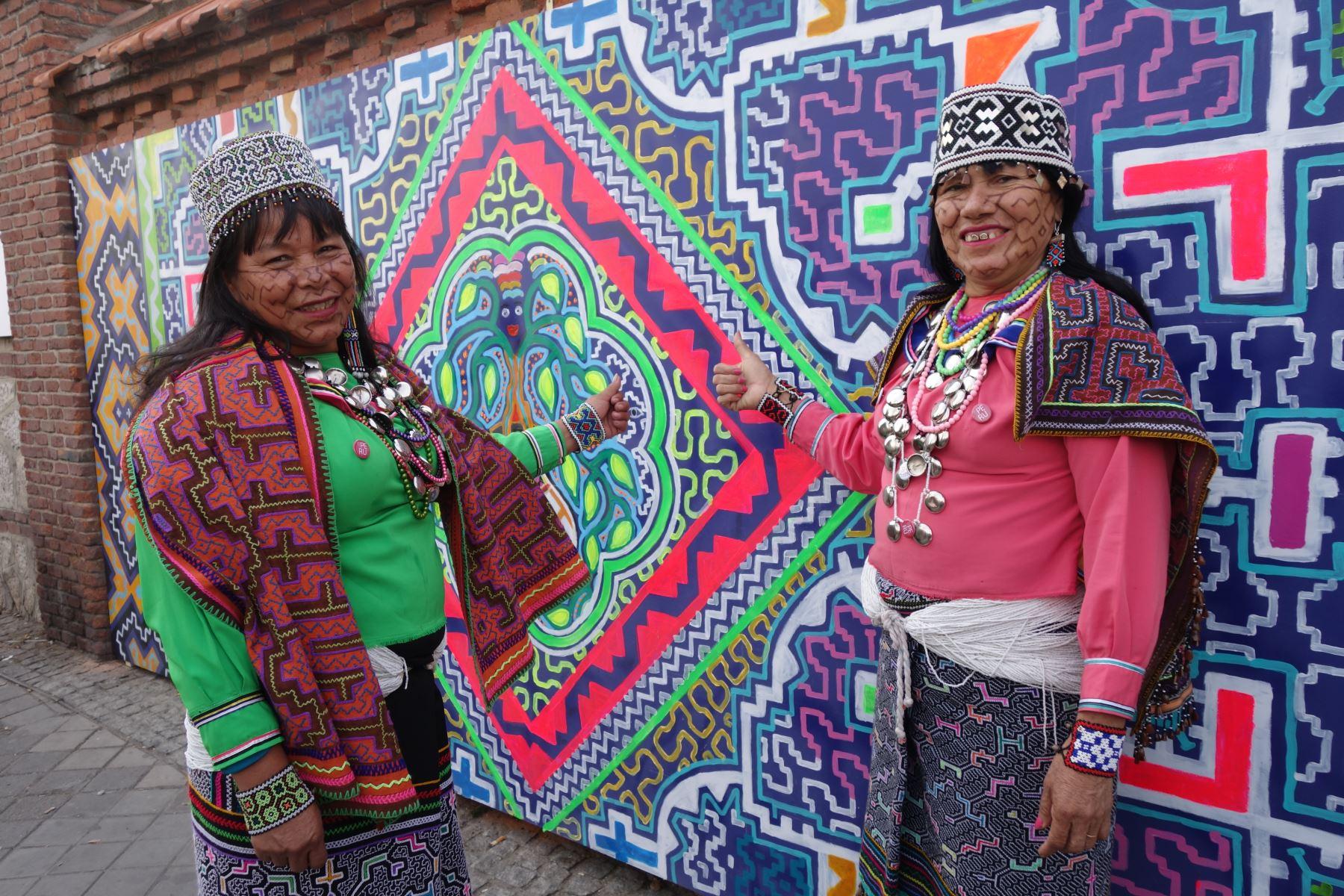 Silvia Ricopa y Olinda Silvano muestran el mural de arte kené shipo-konibo que elaboraron en Madrid.