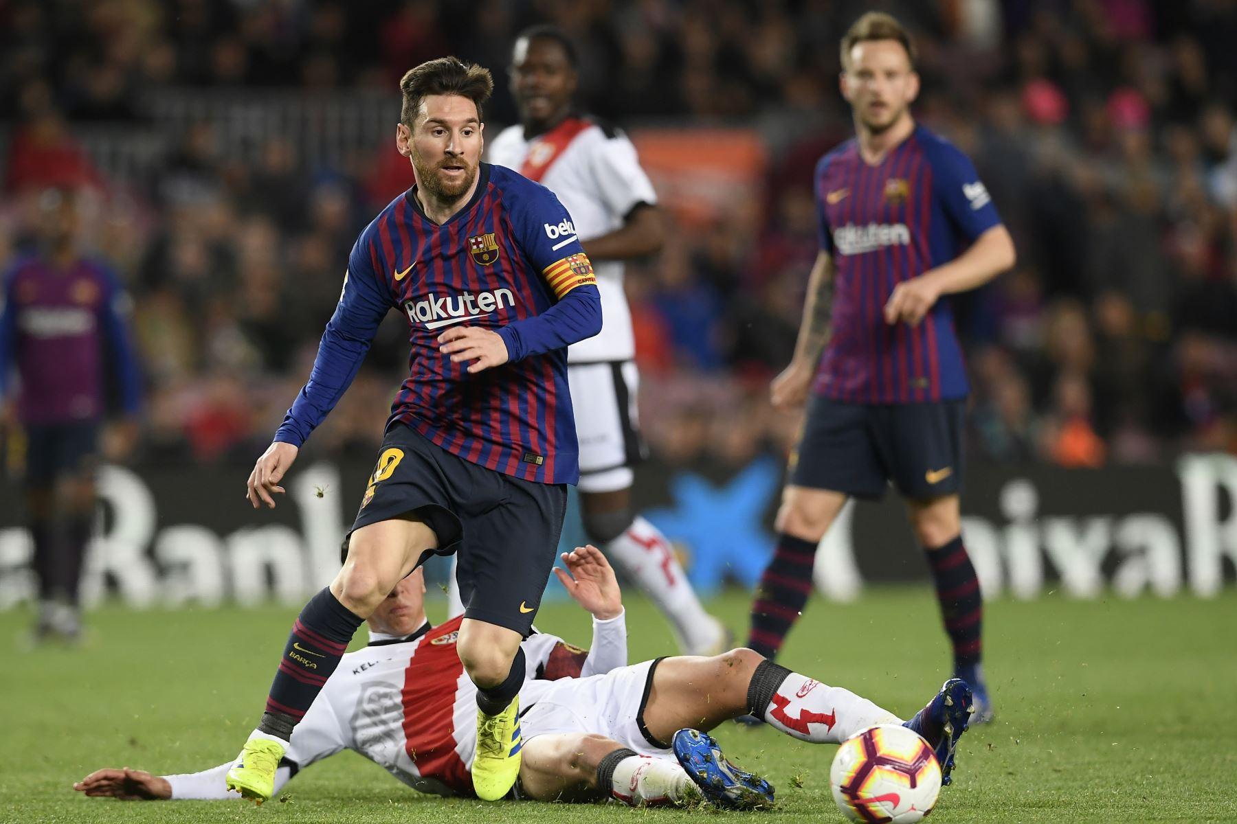 El delantero argentino del Barcelona Lionel Messi (L) compite por el balón con el centrocampista español del Rayo Vallecano Santi Comesana durante el partido de fútbol de la liga española entre el FC Barcelona y el Rayo Vallecano.Foto:AFP