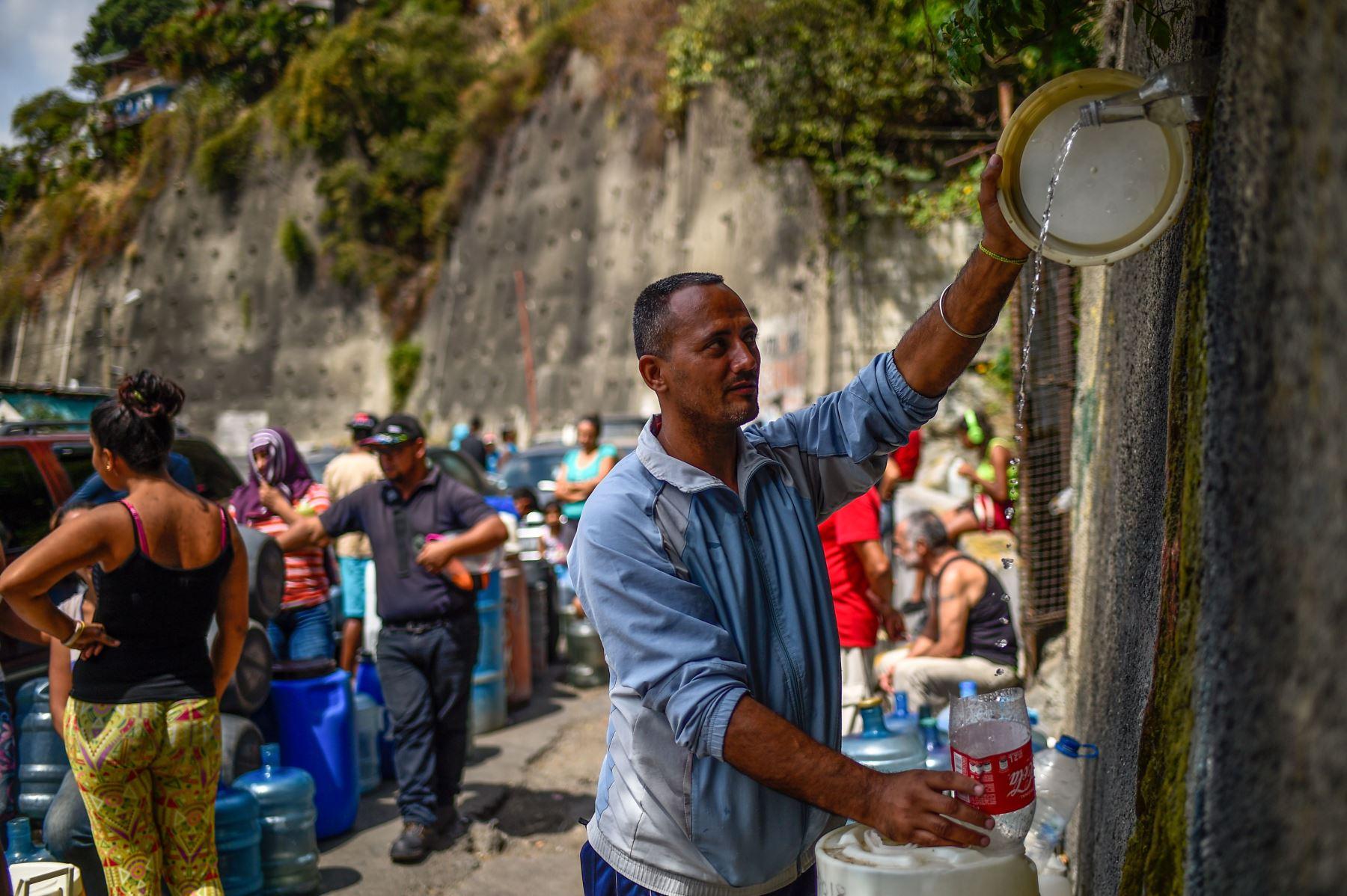 """Caracas: un hombre llena contenedores con agua que fluye desde la montaña Wuaraira Repano, también llamada """"El Ávila"""", en Caracas el 13 de marzo de 2019. Foto: AFP"""