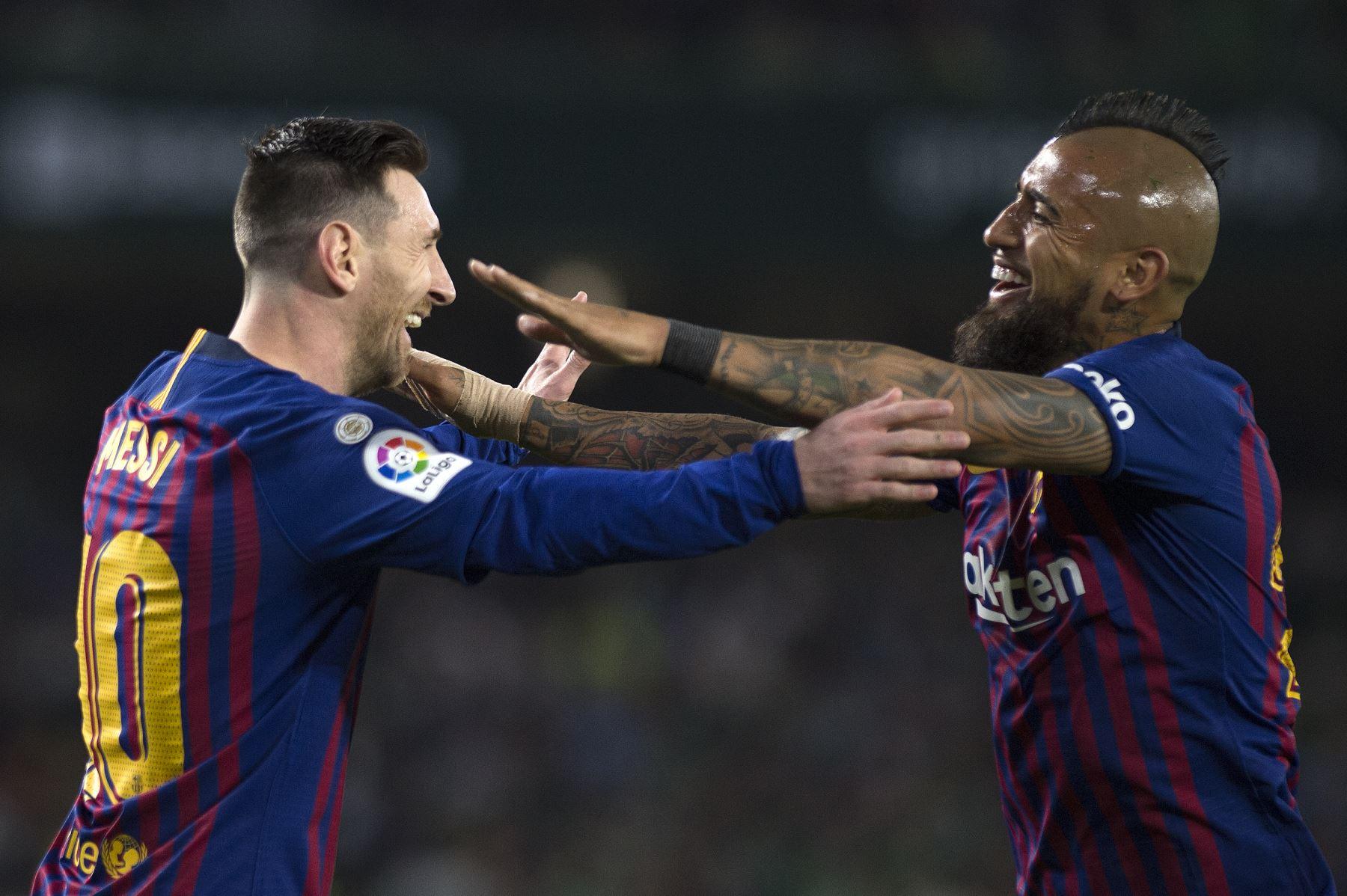 El delantero argentino del Barcelona Lionel Messi (L) celebra su gol con el mediocampista chileno Arturo Vidal durante el partido de fútbol de la liga española entre el Real Betis y el FC Barcelona.Foto:AFP