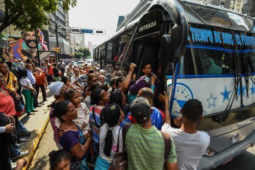 El 25 de marzo de 2019, la gente hace cola para subirse a un autobús durante un corte de energía parcial en Caracas. Foto: AFP
