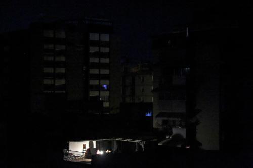 La gente se sienta alrededor de una lámpara de luz afuera de su casa durante un apagón en Caracas el 25 de marzo de 2019. Foto: AFP