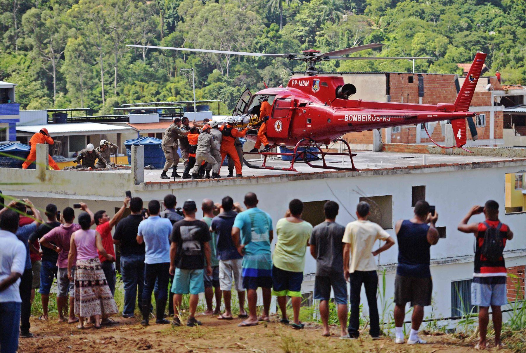 La gente observa cómo una persona lesionada es llevada en un helicóptero de rescate luego de que dos edificios colapsaran en Muzema, Río de Janeiro, Brasil, el 12 de abril de 2019. Foto: AFP