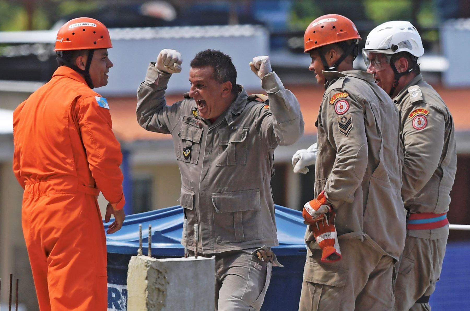 Los rescatistas celebran después de llevar a una persona herida en un colapso de un edificio, en un helicóptero, en Muzema, Río de Janeiro, Brasil, el 12 de abril de 2019. Foto: AFP