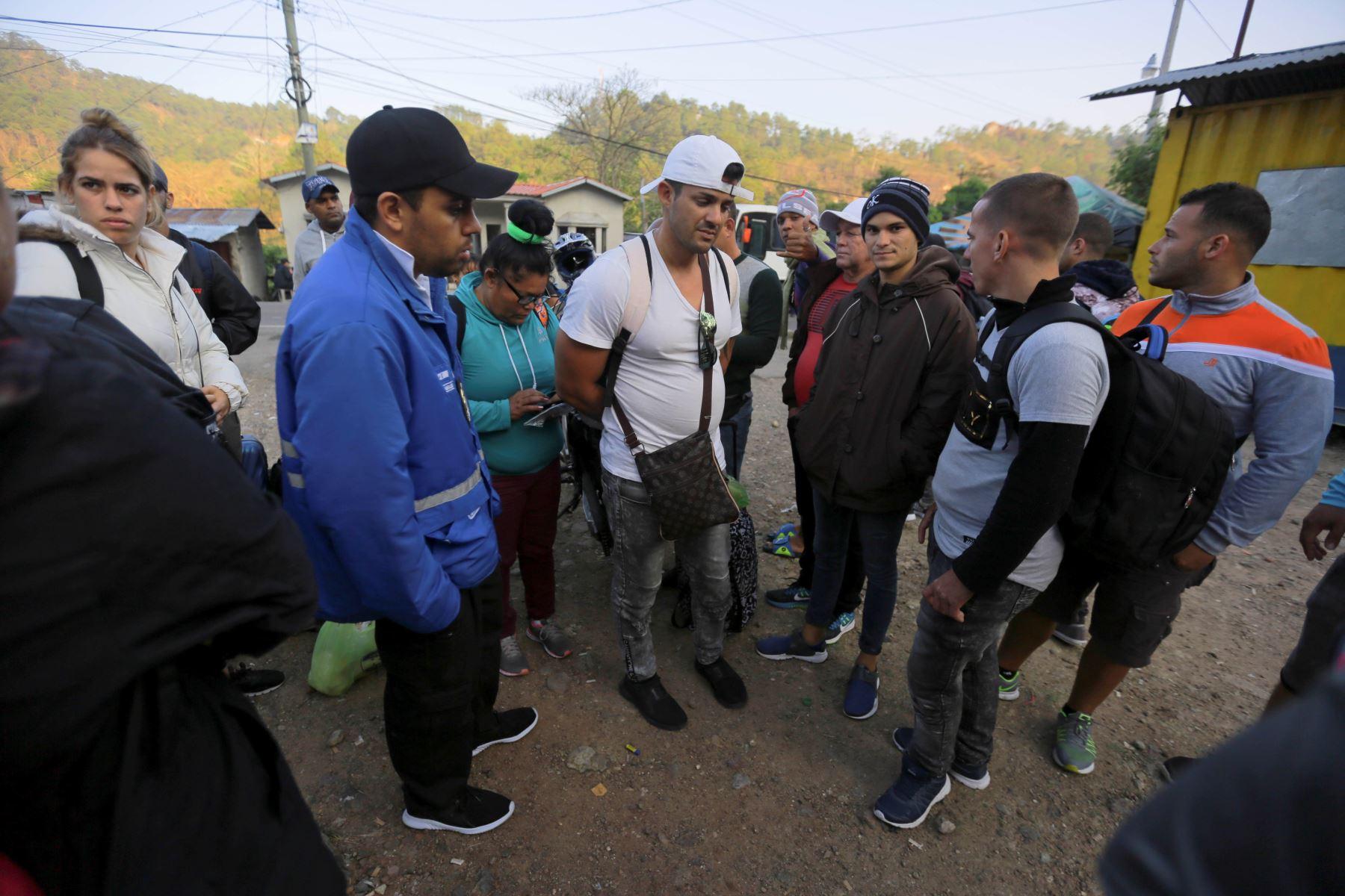 Migrantes cubanos hablan con un agente de migración este viernes al llegar a la Aduana de Agua Caliente (Honduras), fronterizo con Guatemala. Foto: EFE