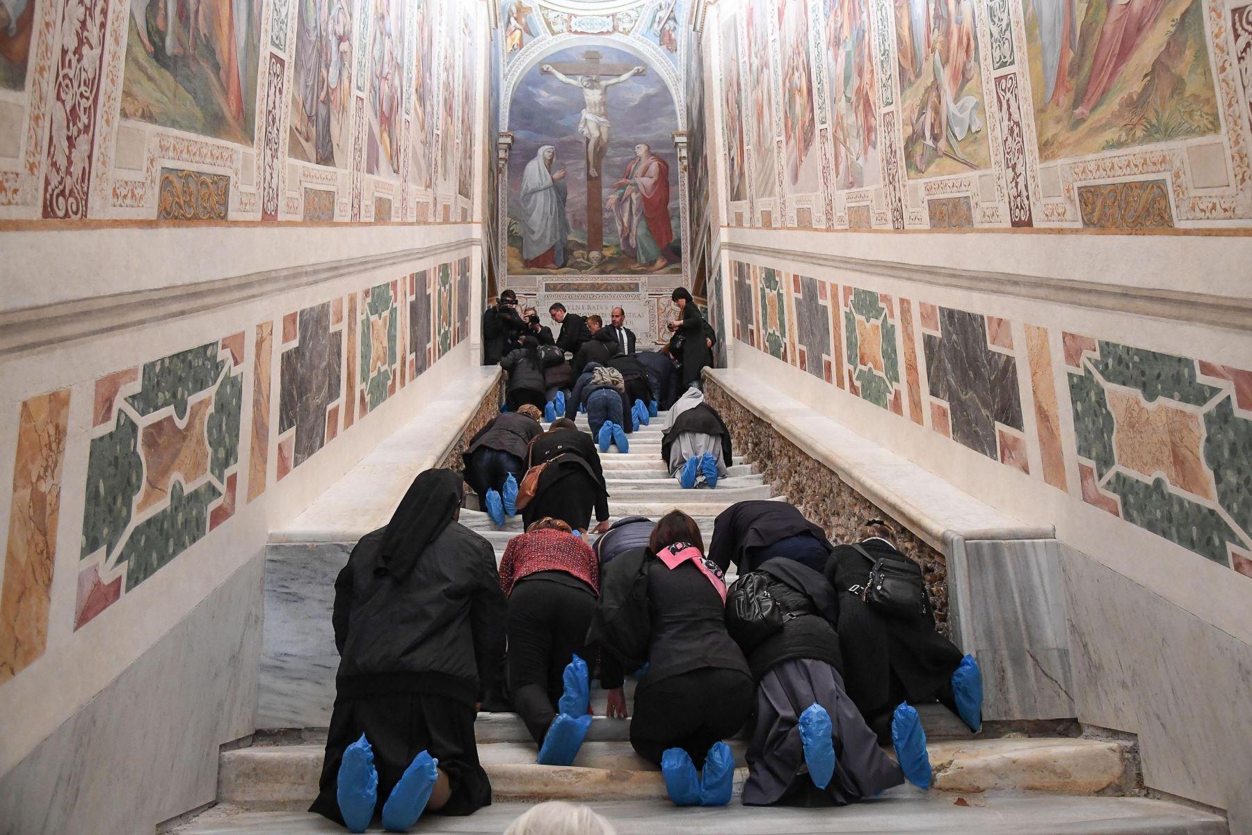 Varias personas recorren de rodillas la Escalera Santa durante su apertura extraordinaria, este jueves en la Basílica de San Juan de Letrán, Roma (Italia). Foto: EFE