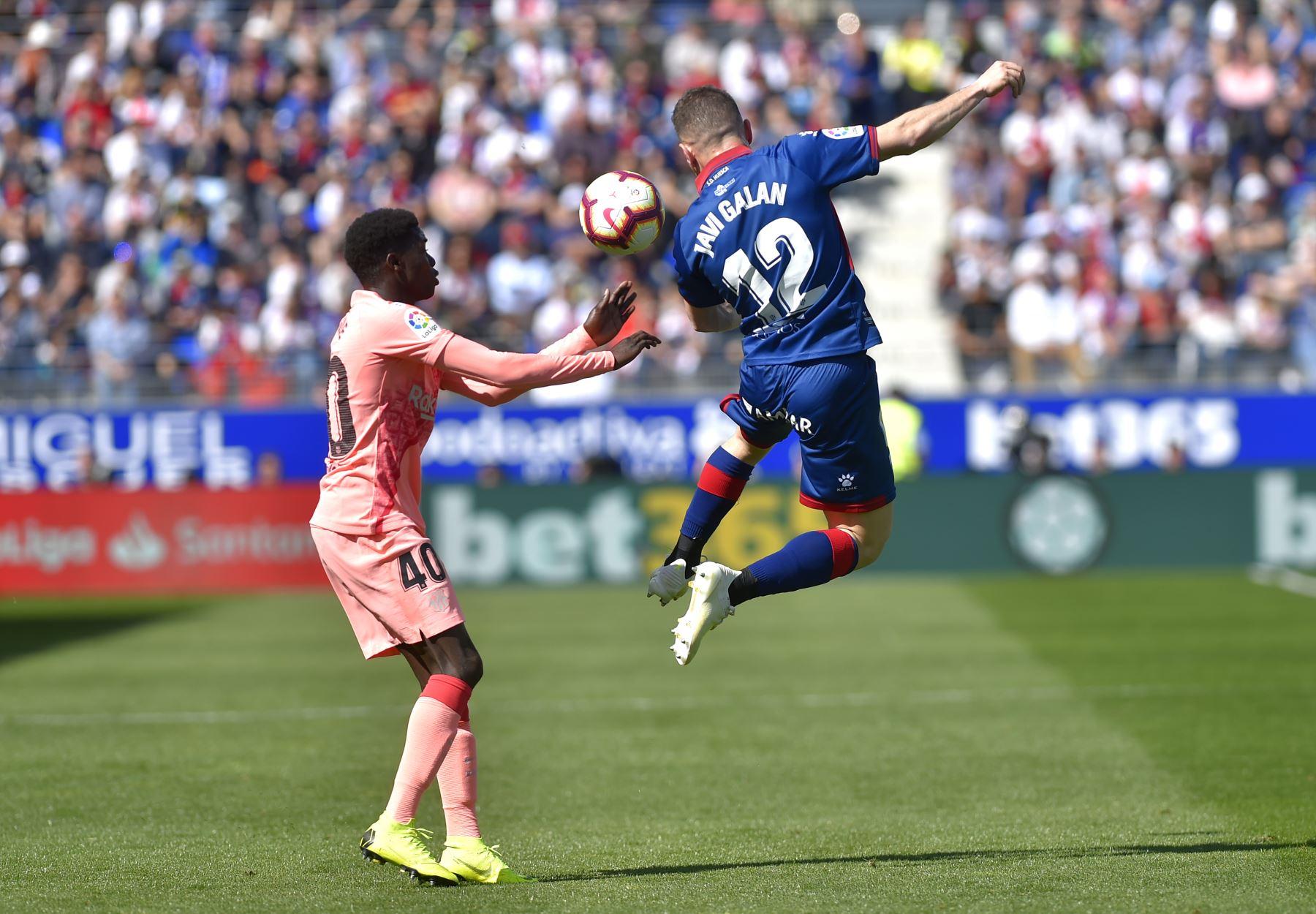 El delantero senegalés del Barcelona, Moussa Wague (L), compite con el mediocampista español del SD Huesca, Javi Galan, durante el partido de fútbol de la liga española entre el SD Huesca y el FC Barcelona.Foto: AFP