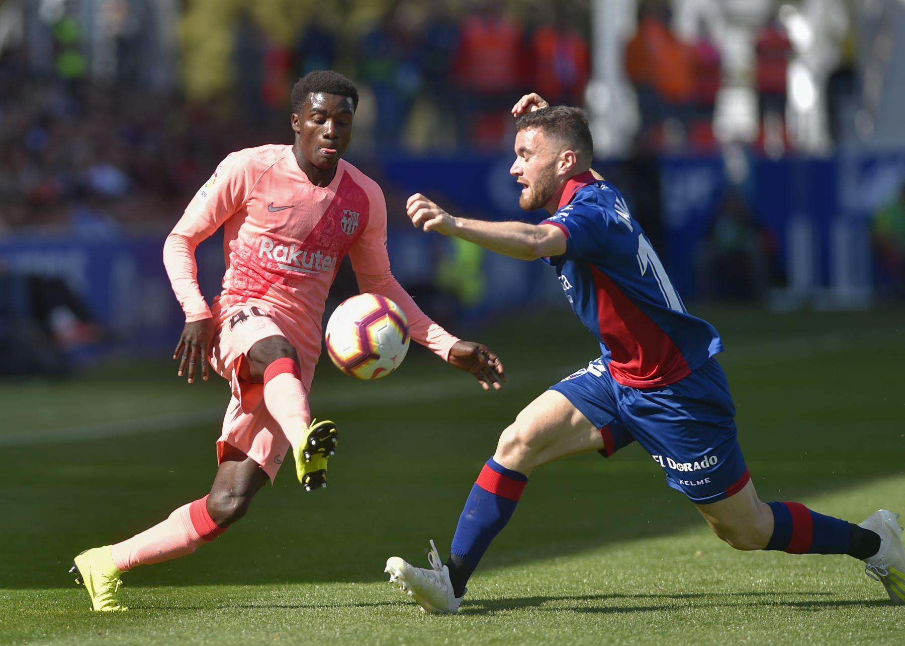 El delantero senegalés de Barcelona Moussa Wague (L) compite con el mediocampista español del SD Huesca, Javi Galan, durante el partido de fútbol de la liga española entre el SD Huesca y el FC Barcelona.Foto:AFP