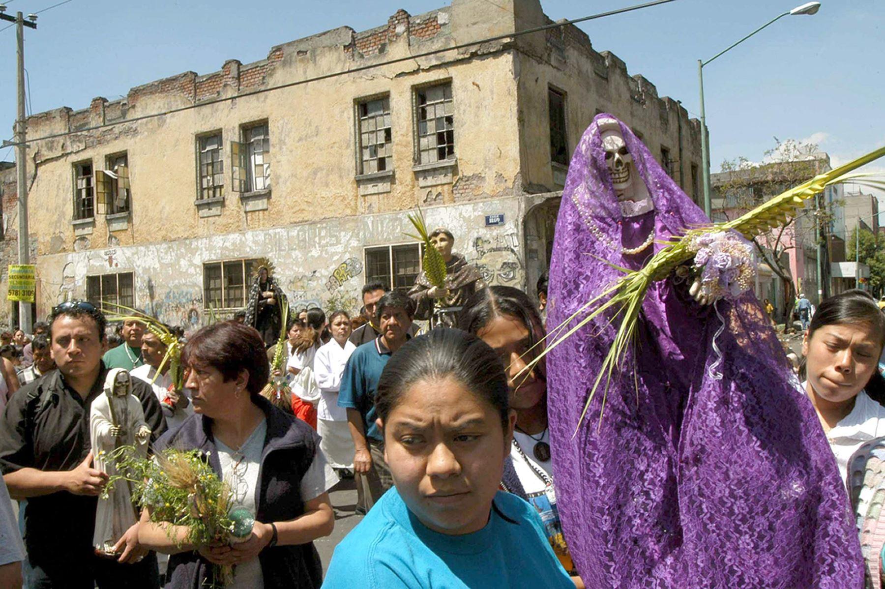 Católicos cargan la imagen de la Santa Muerte mientras caminan en las calles del barrio de Tepito de Ciudad de México, durante una procesión del Domingo de Ramos, en el inicio de la Semana Santa. Foto:AFP