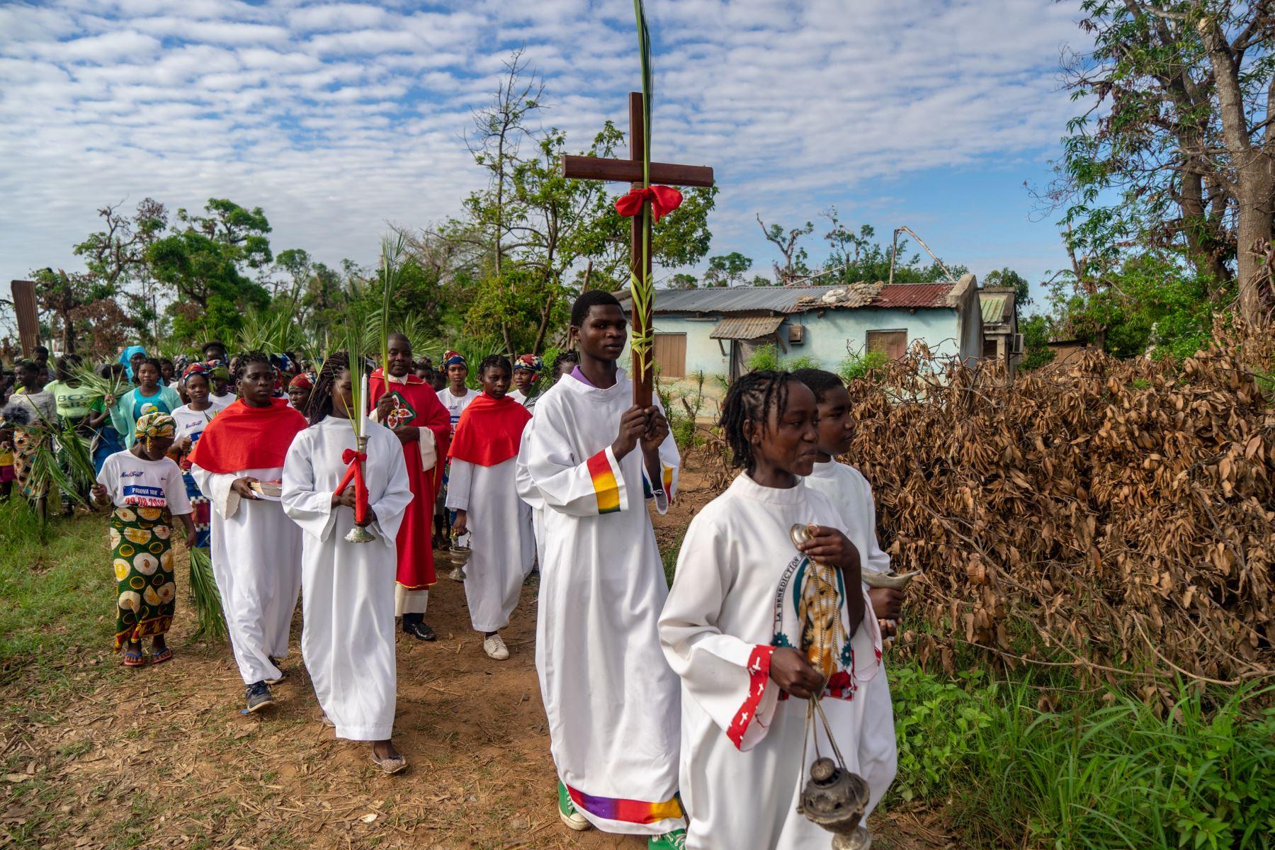 Un congregante sostiene una cruz santa que pasa junto a los escombros durante una marcha para conmemorar el Domingo de Ramos en la Iglesia Católica Parroquial de la Dama de Gracia en Barrio Manasse, distrito de Buzi, provincia de Sofala, Mozambique. Foto : AFP