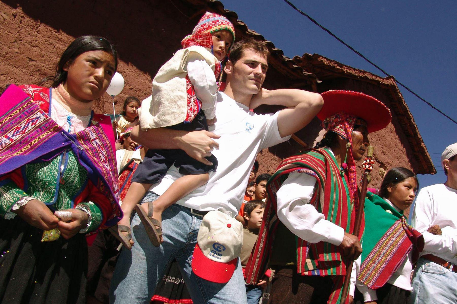 El portero Iker Casillas, lleva a un niño de la comunidad de Patabamba, en Cusco, Perú. Foto: AFP