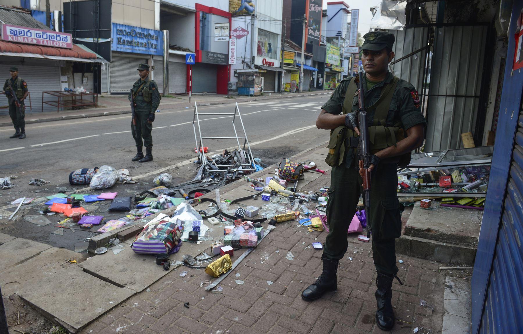 Policías de Sri Lanka hacen guardia frente a una tienda dañada después de un atentado en Sri Lanka. Foto: AFP
