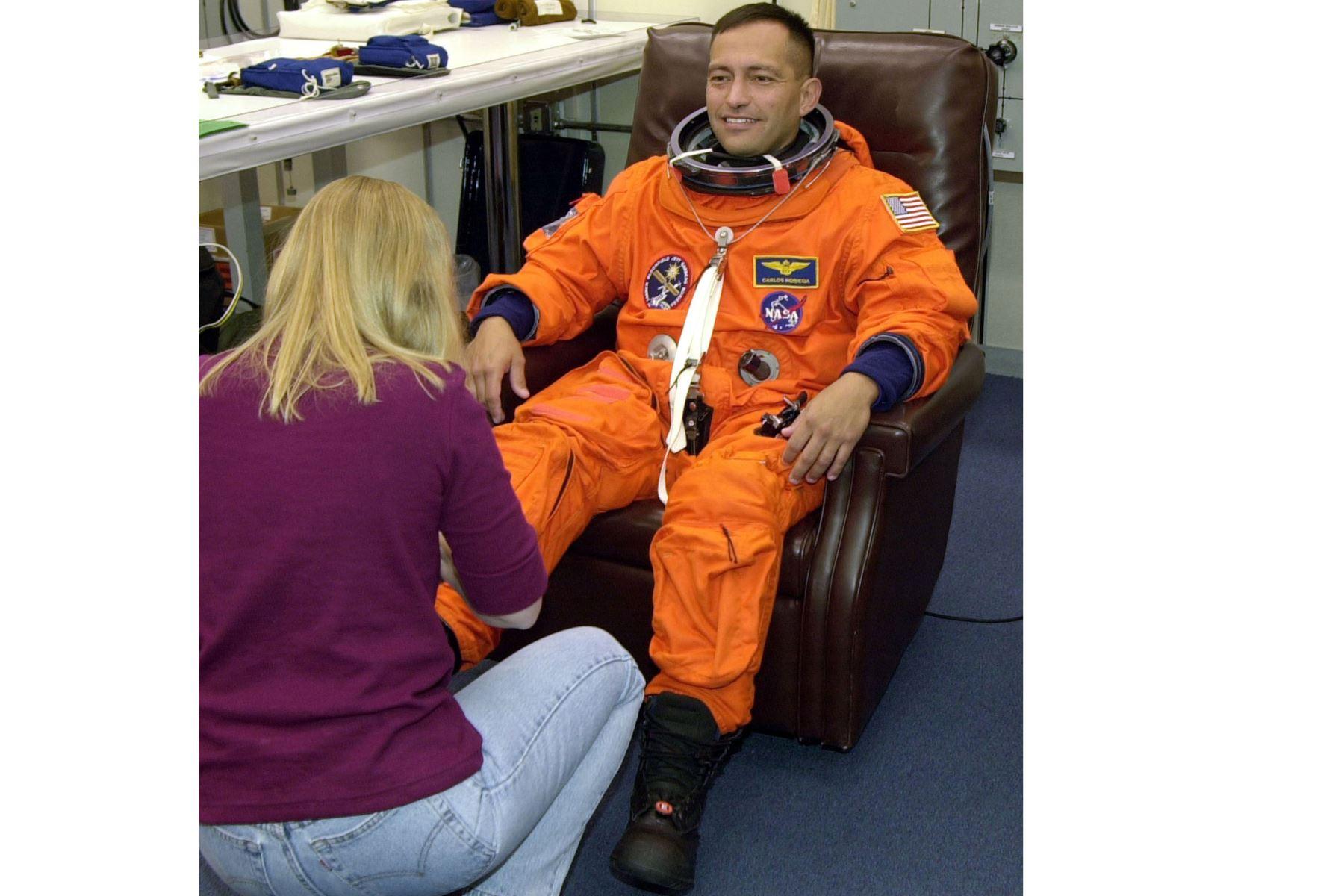 Carlos Noriega, especialista en misiones del transbordador espacial estadounidense, recibe ayuda con sus botas, el 28 de noviembre de 2000, en el Centro Espacial Kennedy, Florida.Foto: AFP