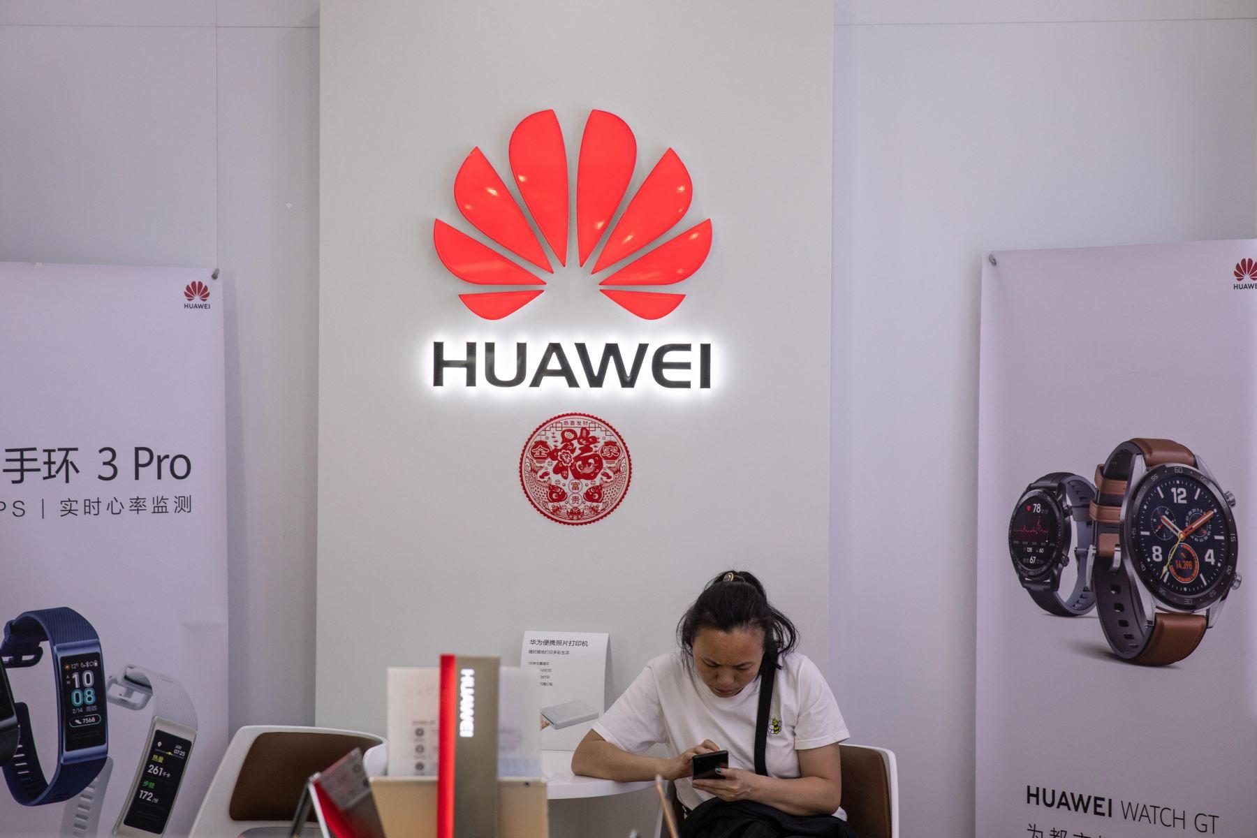 Una mujer usa un teléfono móvil en una tienda de Huawei, este lunes en Pekín (China). El veto de Google y otras tecnológicas estadounidenses a Huawei podría frustrar la aspiración del fabricante chino de convertirse en breve en el mayor fabricante de móviles del mundo. Foto: EFE