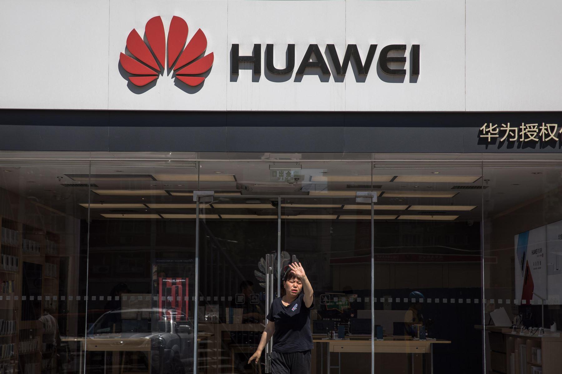 Una dependienta indica a un fotógrafo que no haga fotos del exterior de una tienda de Huawei, este lunes en Pekín (China). Foto: EFE