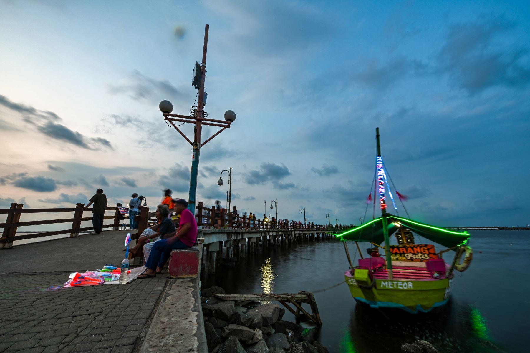 Los indonesios disfrutan de la puesta de sol en la bahía de Yakarta, un día antes del Día Mundial de los Océanos.  El Día Mundial de los Océanos es una forma de celebrar, proteger y conservar los océanos del planeta y sus recursos. Foto:AFP