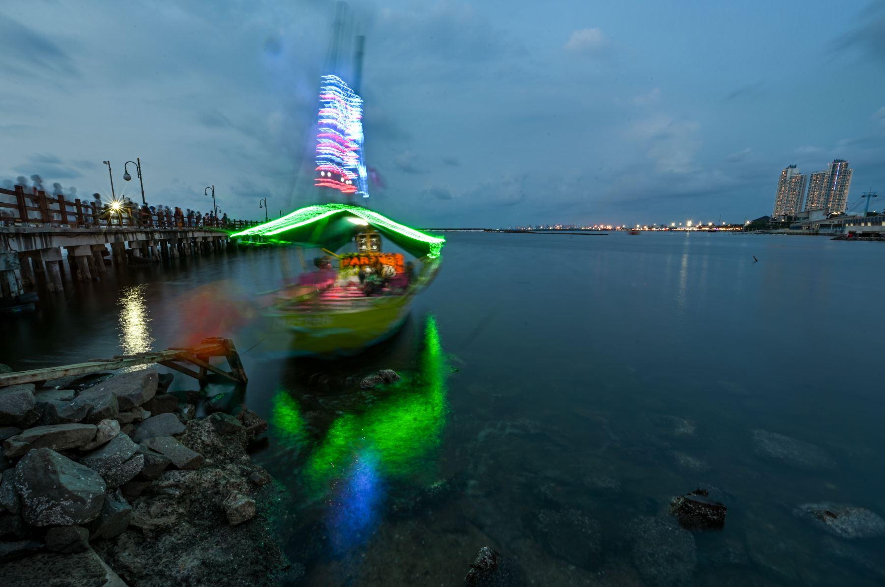 Los indonesios disfrutan de la puesta de sol en la bahía de Yakarta un día antes del Día Mundial de los Océanos.  El Día Mundial de los Océanos es una forma de celebrar, proteger y conservar los océanos del planeta y sus recursos. Foto:AFP