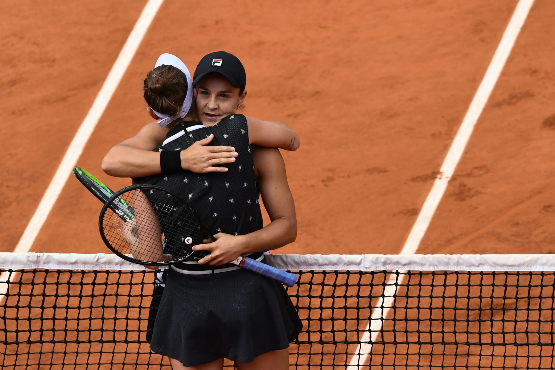 Ashleigh Barty (trasero) de Australia abraza a Marketa Vondrousova de República Checa después de ganar en su partido final de individuales femenino del torneo de tenis Roland Garros 2019. Foto:AFP