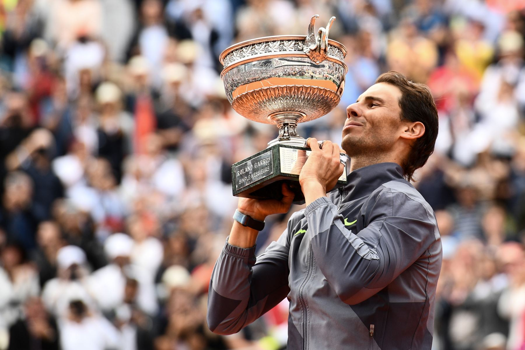 El español Rafael Nadal muerde la Mousquetaires Cup (The Mosqueteros) cuando se presenta al final de la final de individuales masculinos contra el dominic Thiem de Austria del torneo de tenis Roland Garros 2019. Foto:AFP