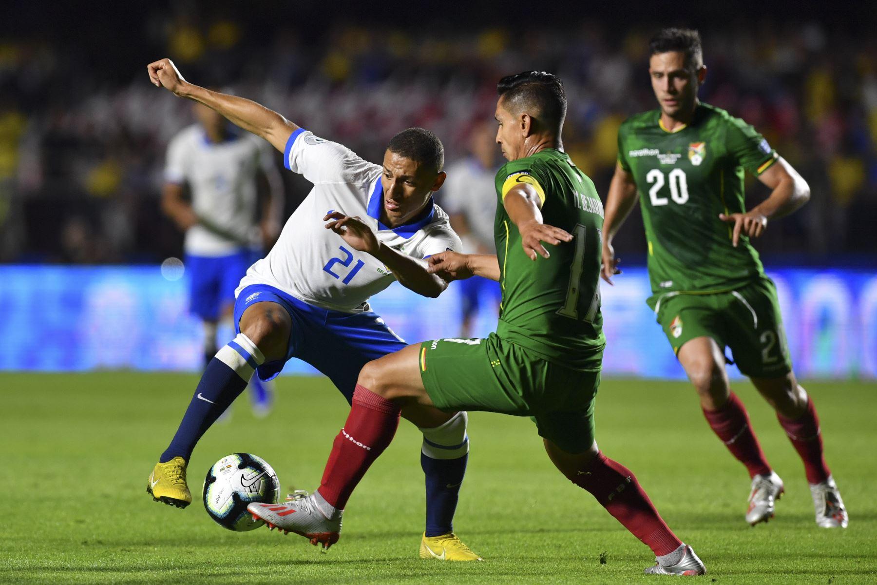 Richarlison (L) de Brasil y Marvin Bejarano de Bolivia compiten por el balón durante su partido de torneo de fútbol de la Copa América en el estadio Morumbi, en Sao Paulo, Brasil