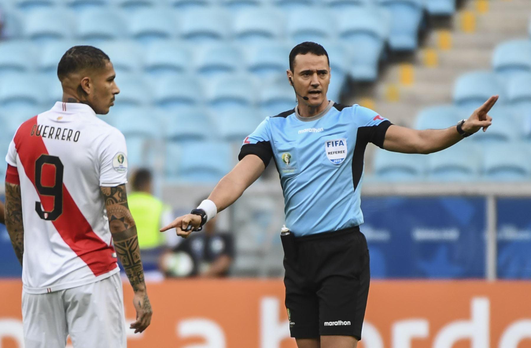 El árbitro colombiano Wilmar Roldan (R) señala al piloto peruano Paolo Guerrero mientras conduce el partido de torneo de fútbol de la Copa América entre Venezuela y Perú en el Gremio Arena en Porto Alegre. Foto: AFP