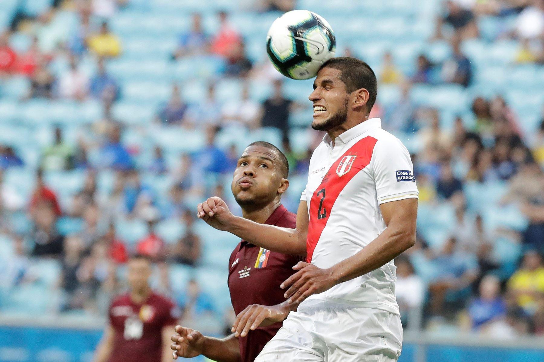 Luis Abram (d) de Perú salta por el balón durante el partido Venezuela-Perú del Grupo A de la Copa América de Fútbol 2019, en el Estadio Arena de Grémio de Porto Alegre, Brasil. Foto:EFE