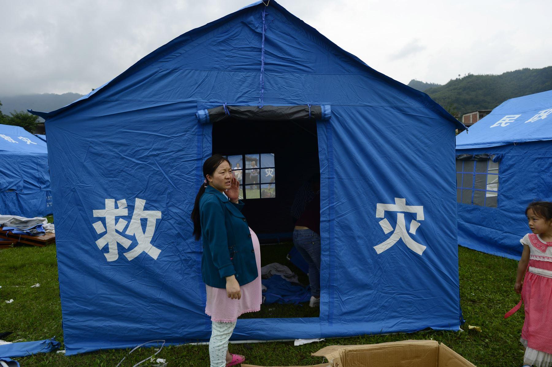 Una mujer embarazada está parada frente a una tienda de campaña en un campamento temporal establecido para sobrevivientes del terremoto en Yibin. Foto: AFP