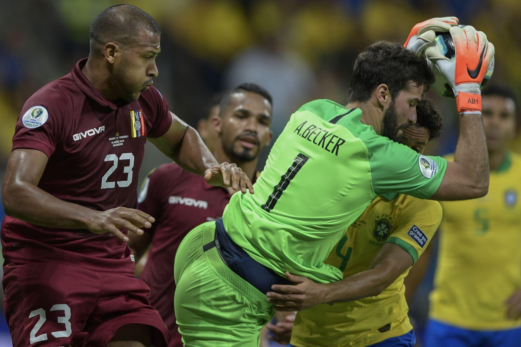 El portero de Brasil, Alisson (R), atrapa el balón junto al Salomon Rondon de Venezuela durante su partido de torneo de fútbol de la Copa América. Foto: AFP