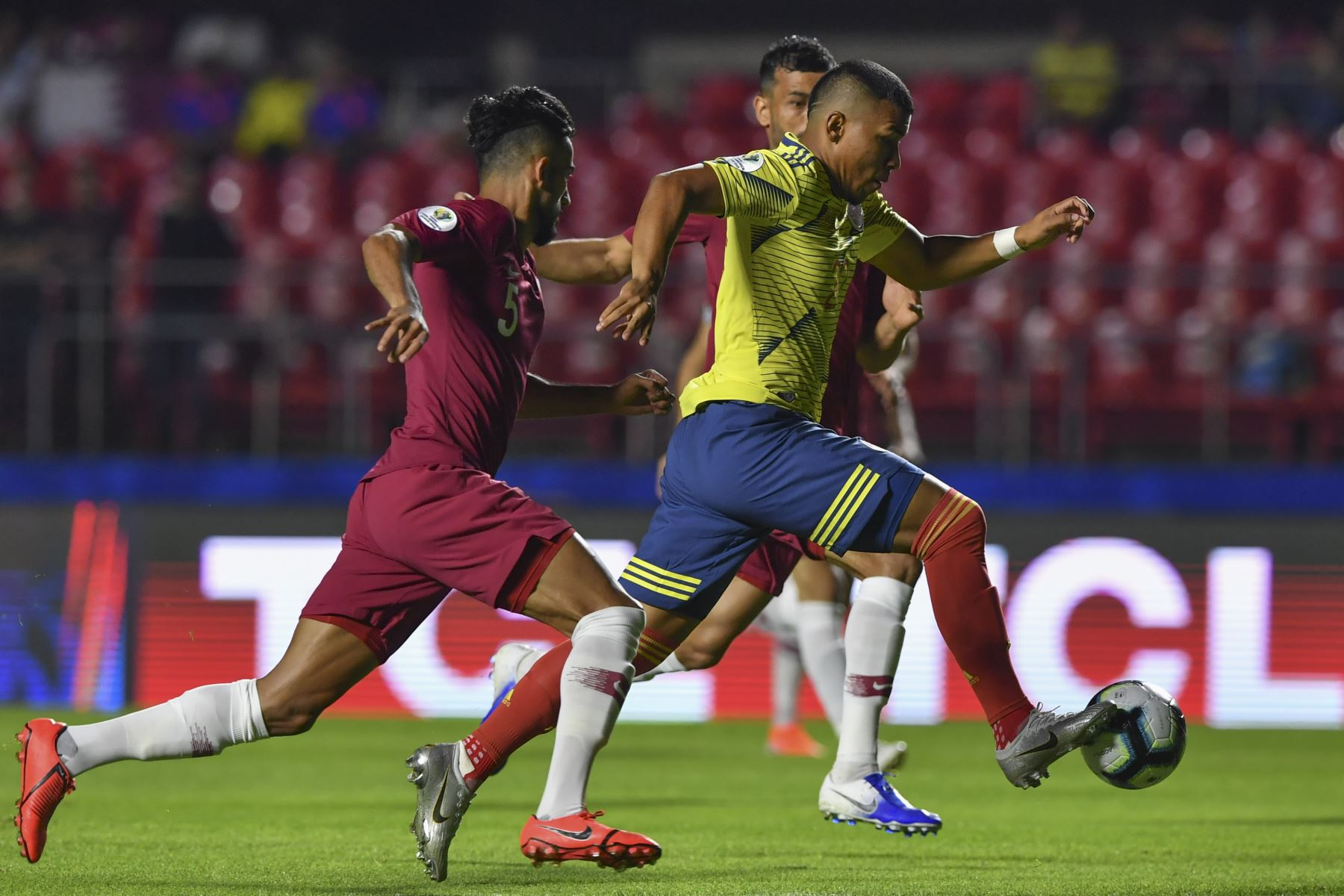 Roger Martinez (R) de Colombia está marcado por Tareq Salman (L) de Qatar durante su partido de torneo de fútbol de la Copa América en el estadio Cicero Pompeu de Toledo, también  2019. Foto : AFP