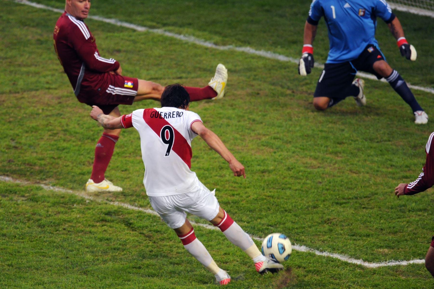 El delantero peruano Paolo Guerrero dispara para marcar el segundo gol de su equipo, mientras que los venezolanos José Manuel Rey (L) y el portero Renny Vega reaccionan durante el partido por el tercer lugar del torneo de fútbol de la Copa América 2011 celebrado en el estadio Ciudad de La Plata en La Plata, 59 Km al sur de Buenos Aires, el 23 de julio de 2011.  Foto: AFP