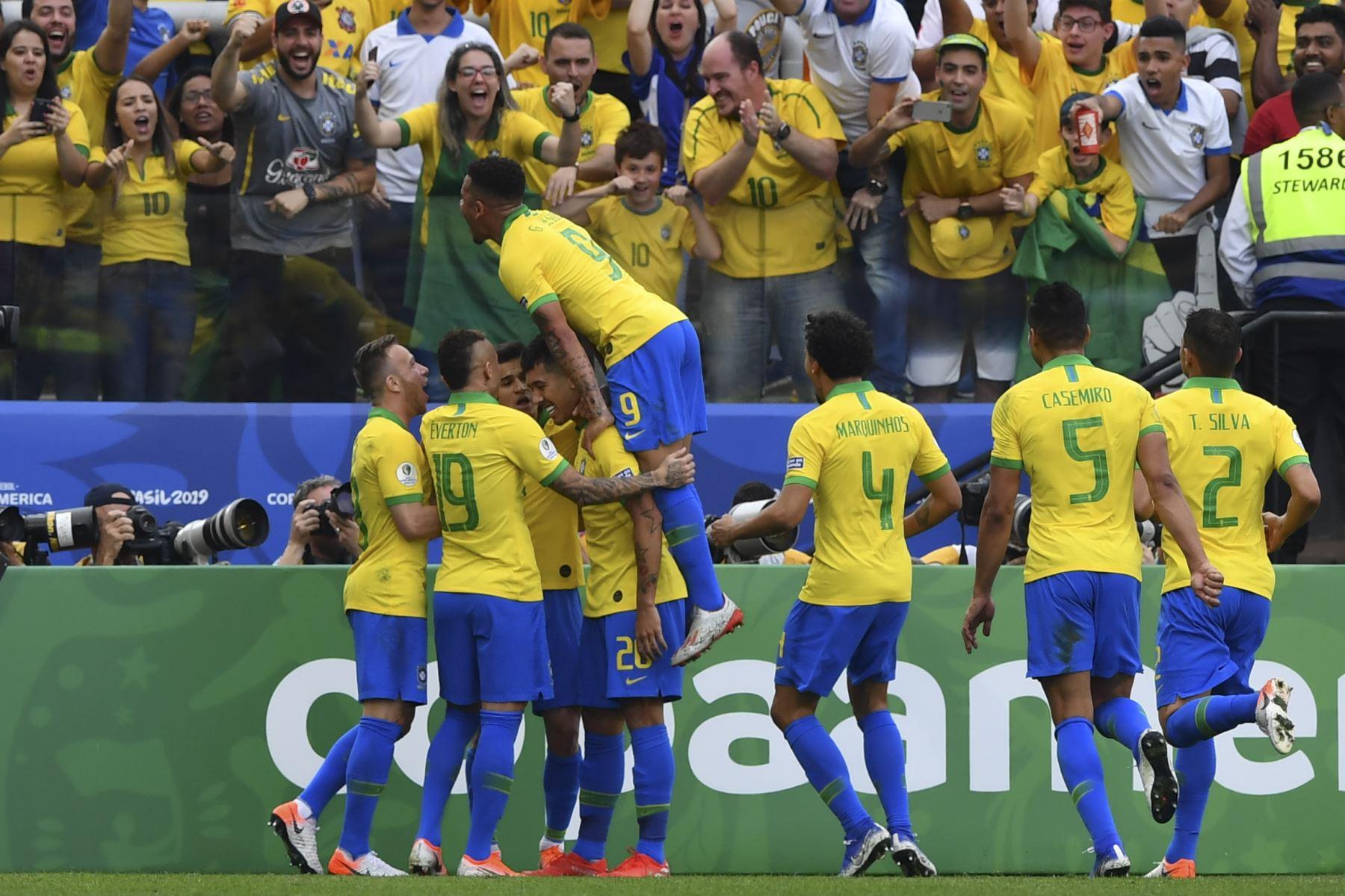 El brasileño Roberto Firmino (20) celebra con sus compañeros de equipo luego de marcar el segundo gol del equipo contra Perú durante su partido de torneo de fútbol de la Copa América. Foto: AFP