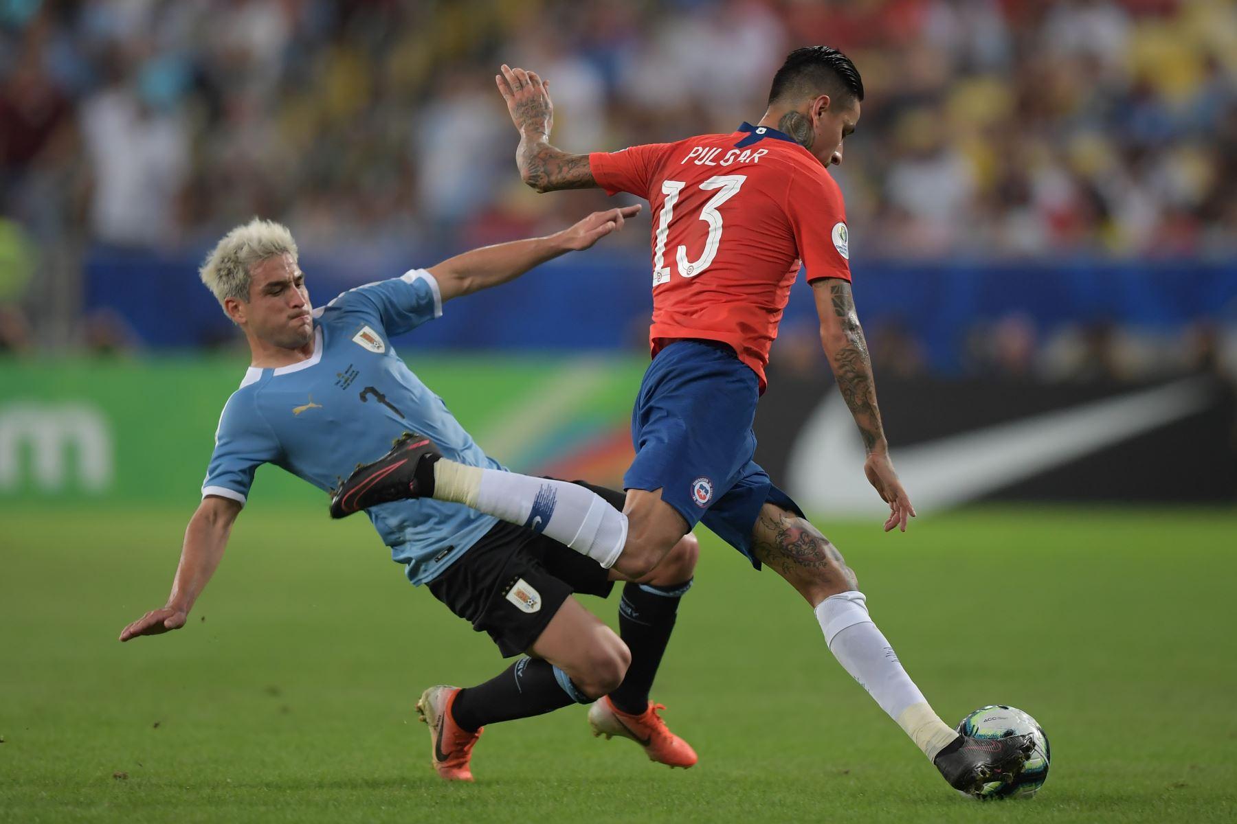 El chileno Erick Pulgar (R) está marcado por el uruguayo Nicolás Lodeiro durante el partido de torneo de fútbol de la Copa América en el estadio Maracana en Río de Janeiro, Brasil.Foto:AFP