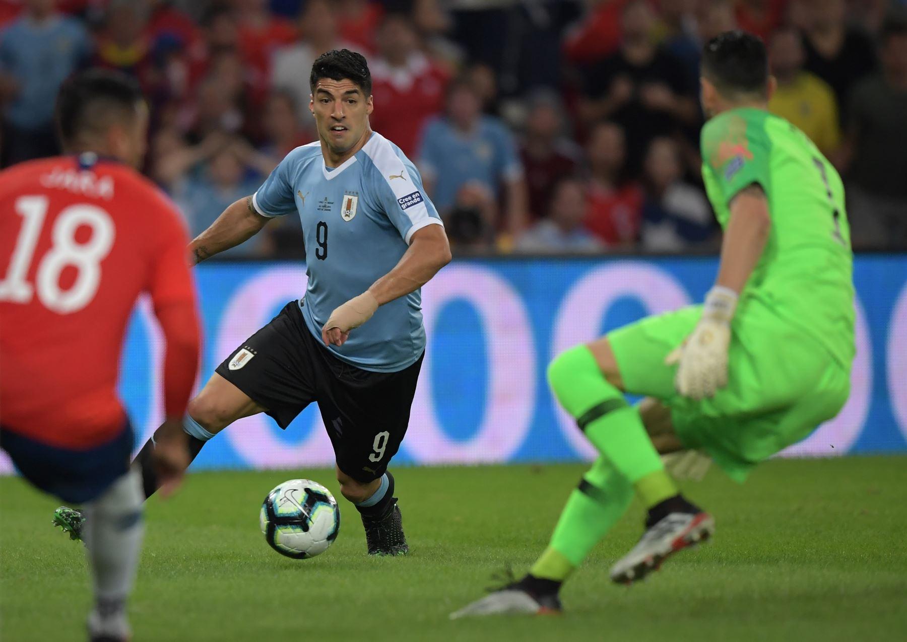 Luis Suárez (R), de Uruguay, trata de anotar a Gonzalo Jara (L) de Chile y al arquero Gabriel Arias durante el partido de torneo de fútbol de la Copa América en el Estadio Maracaná de Río de Janeiro, Brasil.Foto:AFP