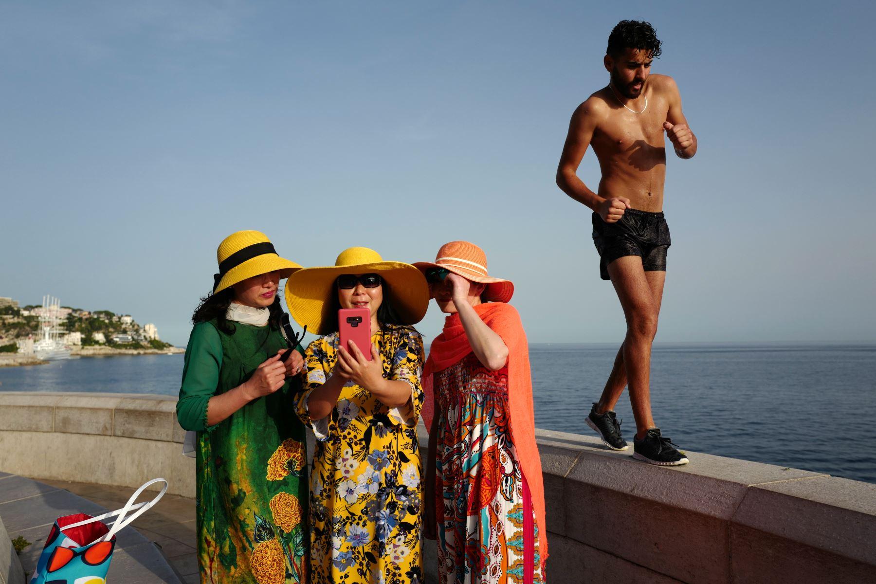 Un hombre pasa mientras los turistas toman selfies en la ciudad de la Riviera francesa de Niza, mientras las temperaturas se elevan a 33 grados centígrados. Foto: AFP