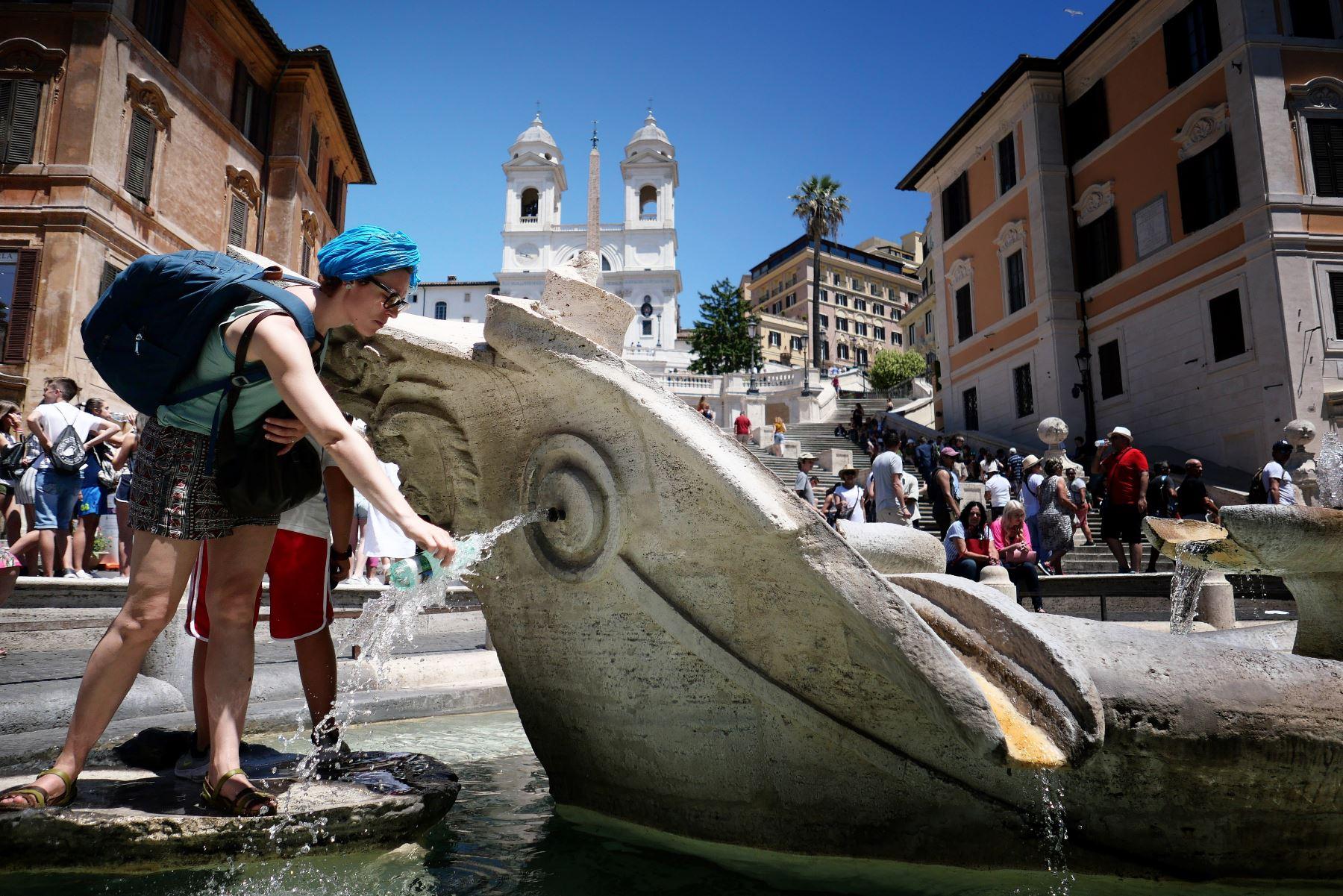 Una turista llena su botella de agua de la Fontana della Barcaccia en Piazzia di Spagna en el centro de Roma durante una inusual ola de calor. Foto: AFP