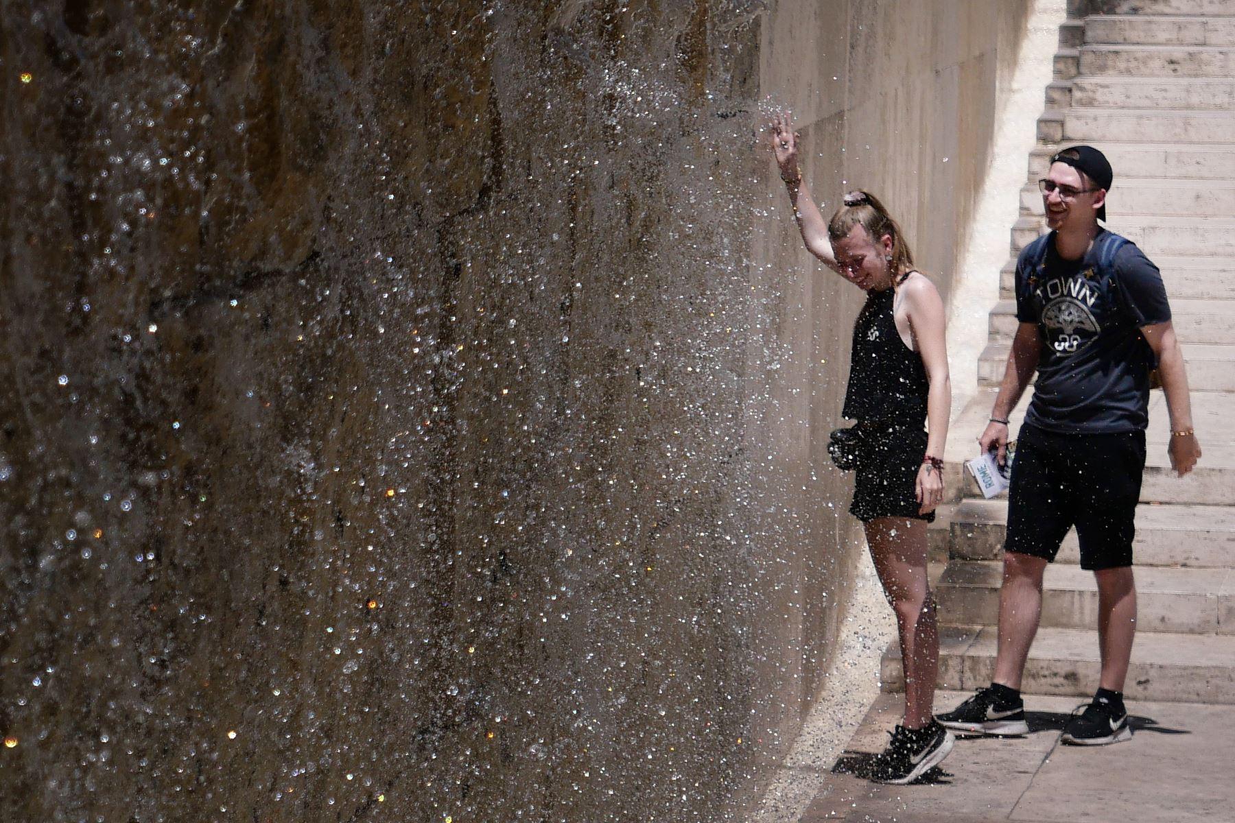 La gente se refresca en una fuente de cascada durante una ola de calor en Roma. Foto: AFP