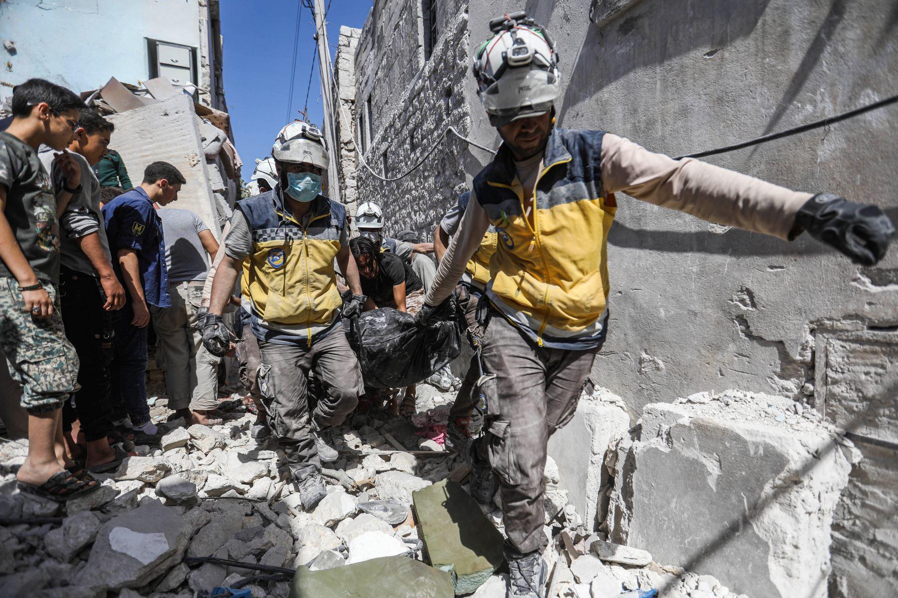 Miembros de la Defensa Civil Siria encuentran víctimas tras un ataque aéreo en la ciudad de Ariha, en el  Siria. Foto: AFP