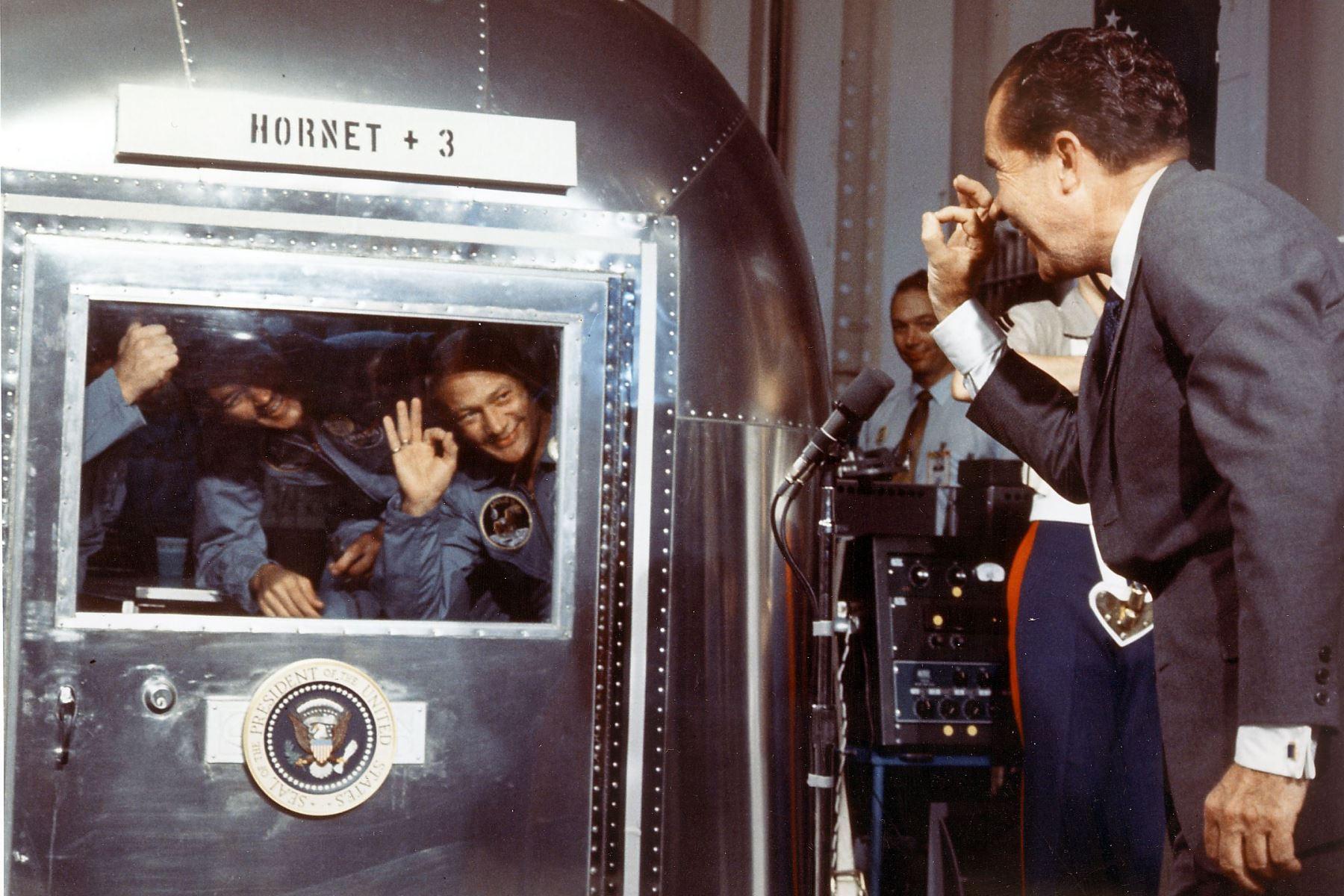 El presidente Richard M. Nixon y los astronautas del Apolo 11 intercambian saludos a través de la ventana de la Instalación de cuarentena móvil. Foto: AFP