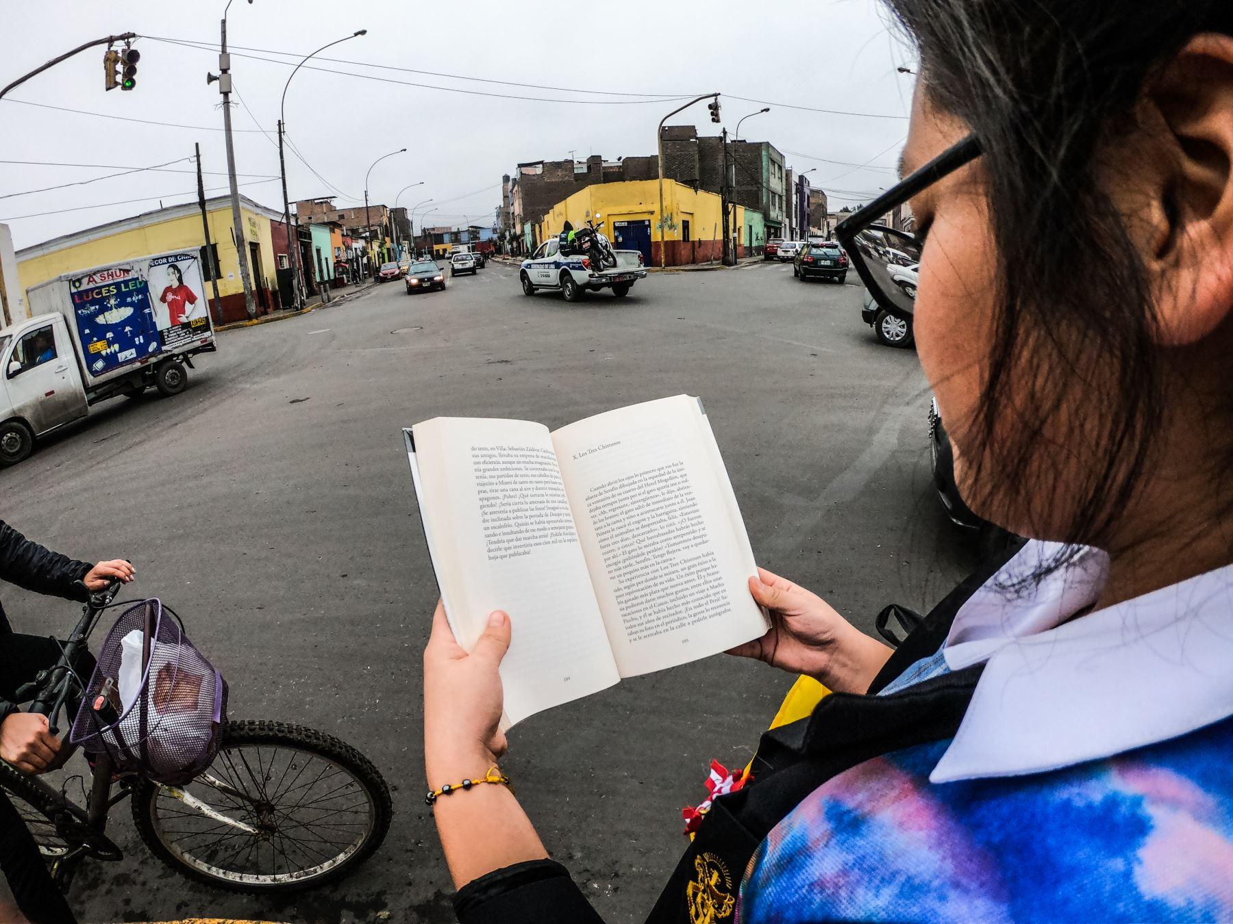 Una niña sostiene el libro cinco Esquinas de Mario Vargas Llosa, Cinco Esquinas, Barrios Altos ANDINA/ José Sotomayor