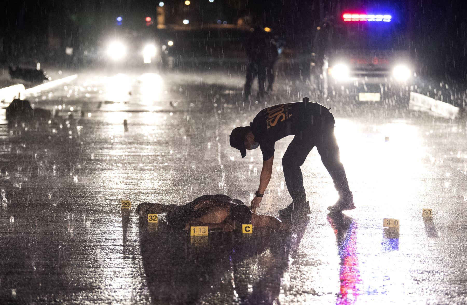 Los oficiales de policía investigan una escena de un tiroteo mientras el cuerpo de un sospechoso yace en una calle en Manila. Tres sospechosos murieron a tiros luego de un intercambio de disparos durante una operación policial, con tres armas de fuego y un saquito de metanfetamina recuperado en la escena. AFP
