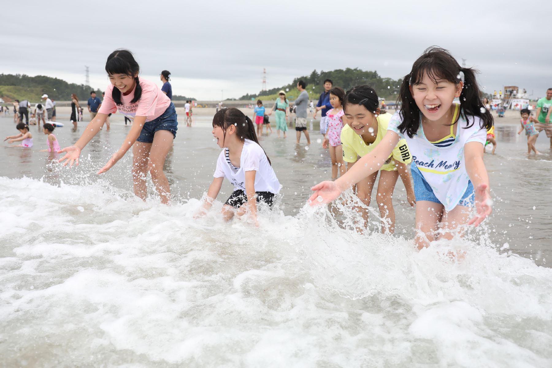 Los niños juegan con las olas durante la apertura de la playa al público en Kita Izumi en la ciudad de Minami Soma, prefectura de Fukushima, La playa estuvo cerrada por más de ocho años después del accidente de la central nuclear de Fukushima Daiichi. AFP