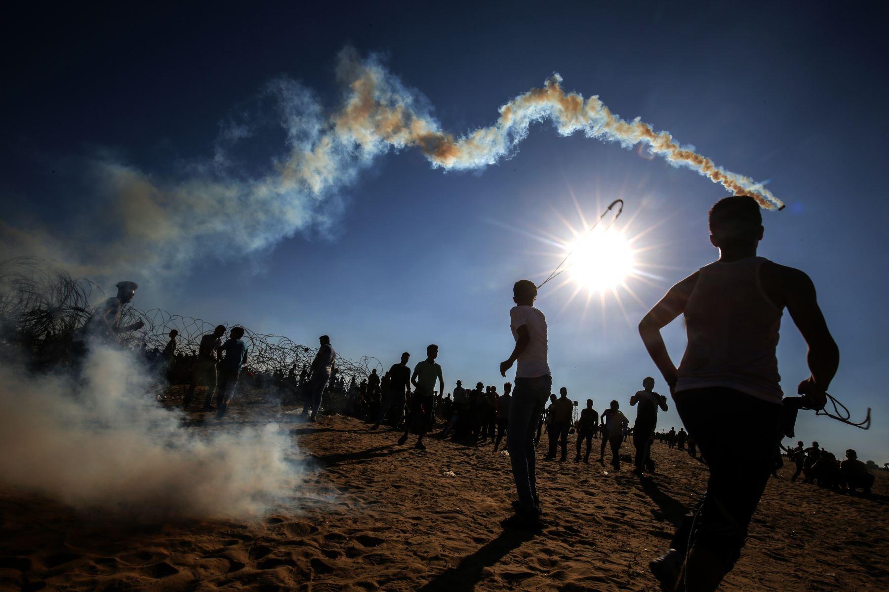 Los jóvenes palestinos usan hondas para lanzar rocas a las tropas israelíes durante los enfrentamientos entre manifestantes palestinos y fuerzas israelíes a través de la cerca de alambre de púas después de una manifestación fronteriza cerca de Rafah en el sur de la Franja de Gaza. AFP