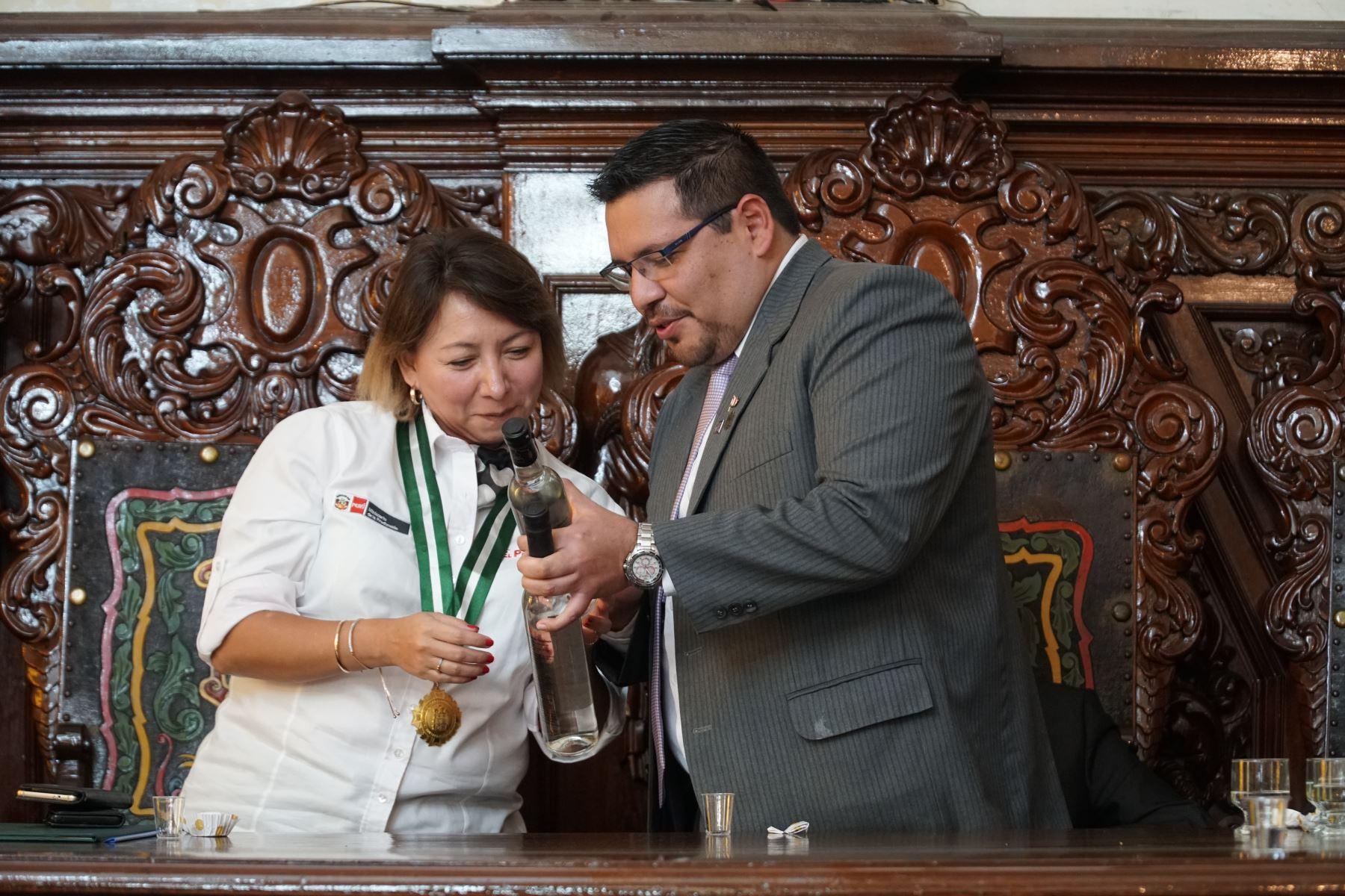 Luis Verdi Ávila, gerente de Desarrollo Económico y Seguridad Ciudadana del Municipalidad Provincial de Ica, entrega una botella de la bebida bandera a la ministra de la Producción. Foto:ANDINA/Cortesía Genry Bautista