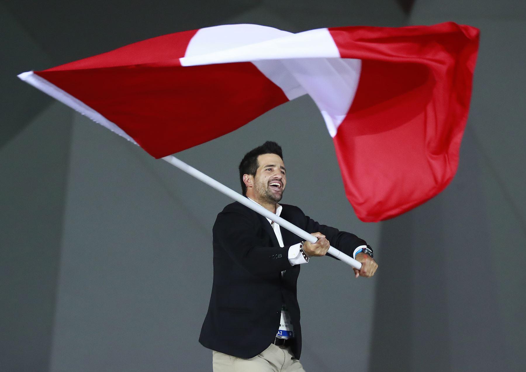 Stefano Peschiera de Perú, ondea la bandera peruana durante la ceremonia de apertura de los Juegos Panamericanos de Lima 2019. Foto: Lima 2019