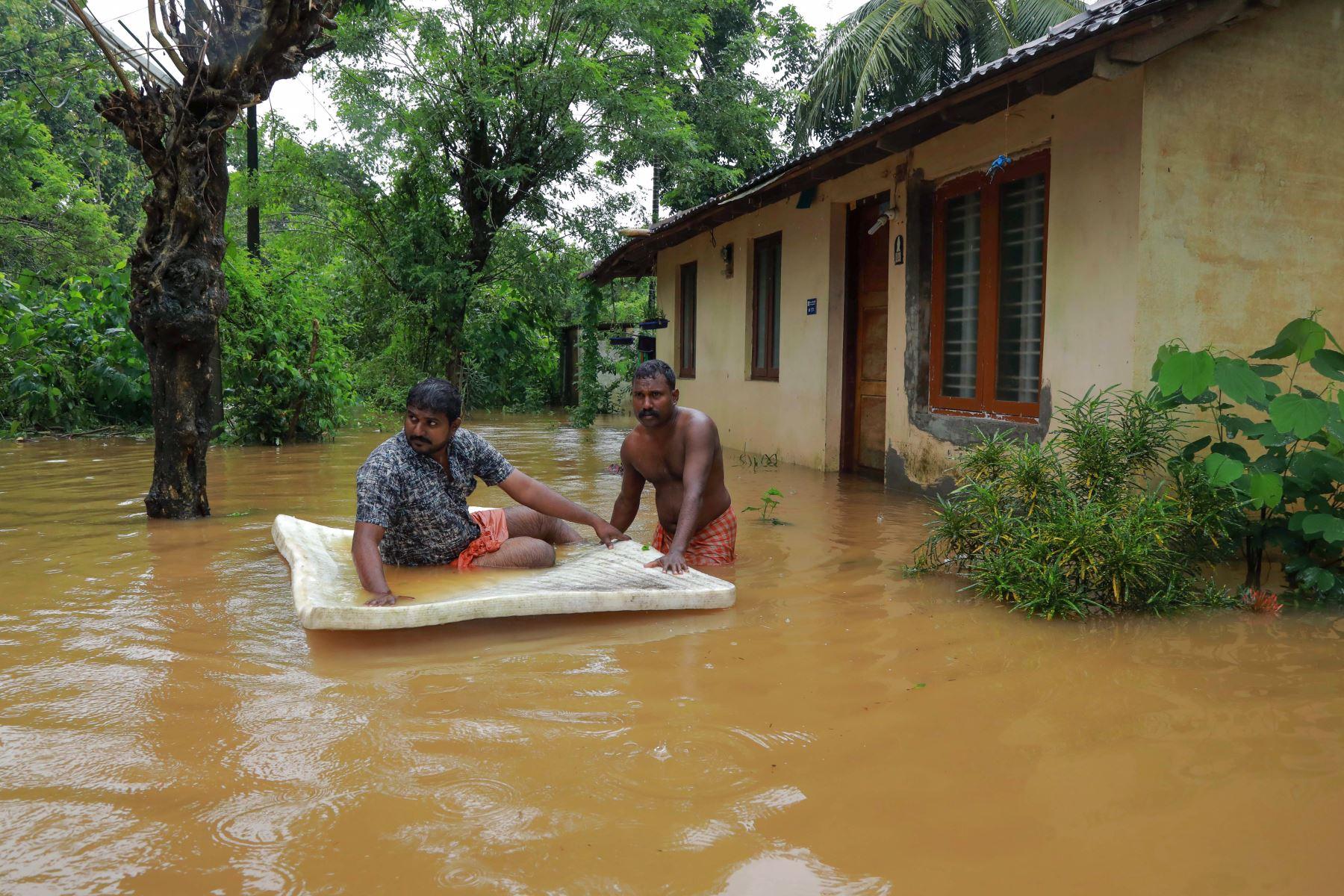 Los hombres pasan por las aguas de la inundación en el área de Eloor en el distrito de Ernakulam, en el estado de Kerala, en el sur de la India. Las inundaciones que han matado a más de 20 personas forzaron el cierre del aeropuerto internacional de Kochi el 9 de agosto como el estado del sur de la India de Kerala se enfrentó a un segundo año consecutivo de lluvias a nivel de crisis. Foto: AFP