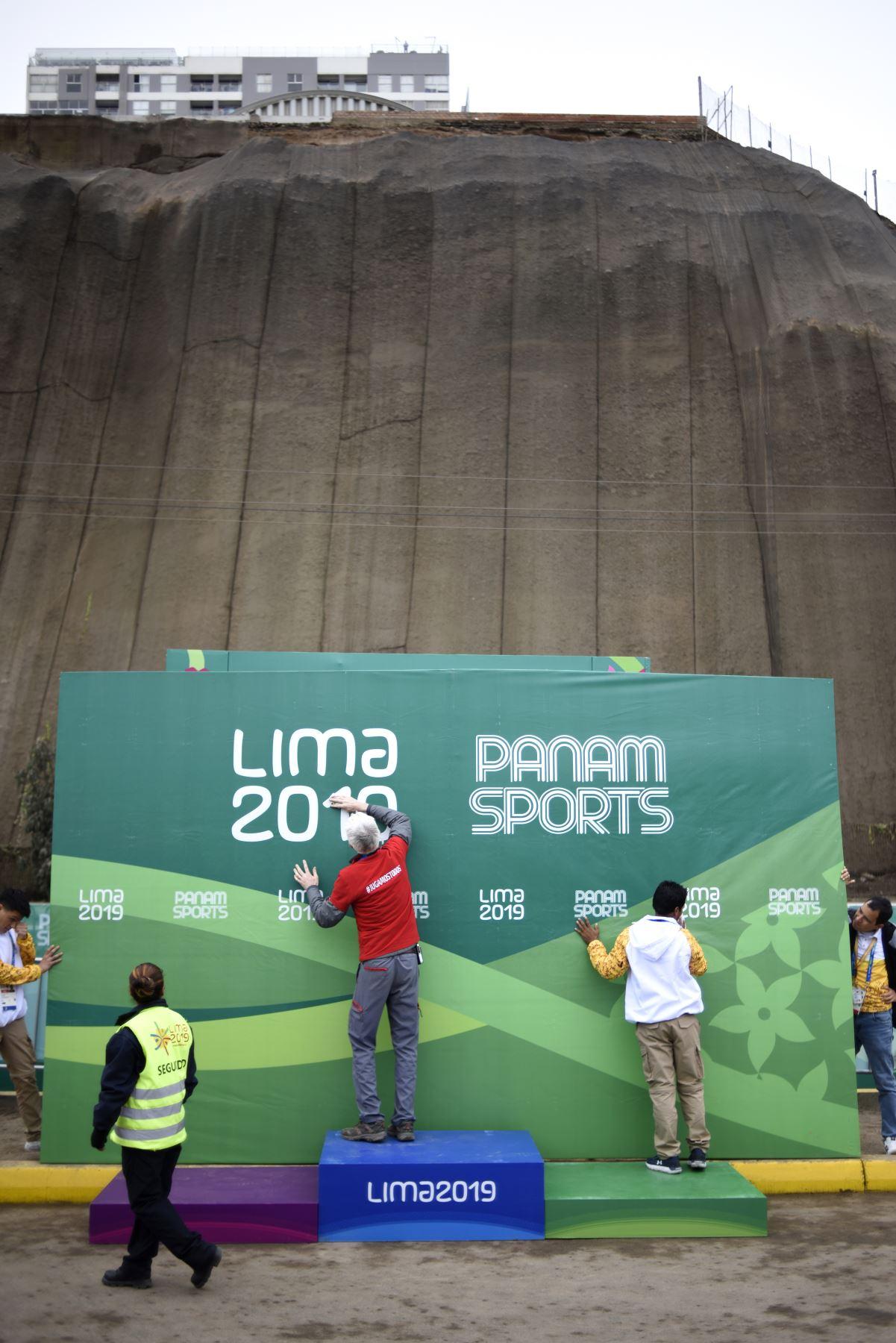 Personal de Lima 2019 limpiando el cartel de los paramericanos previa a la entrega de medallas de Ciclismo de Ruta realizada en la costa verde. Foto: ANDINA/ Lima 2019