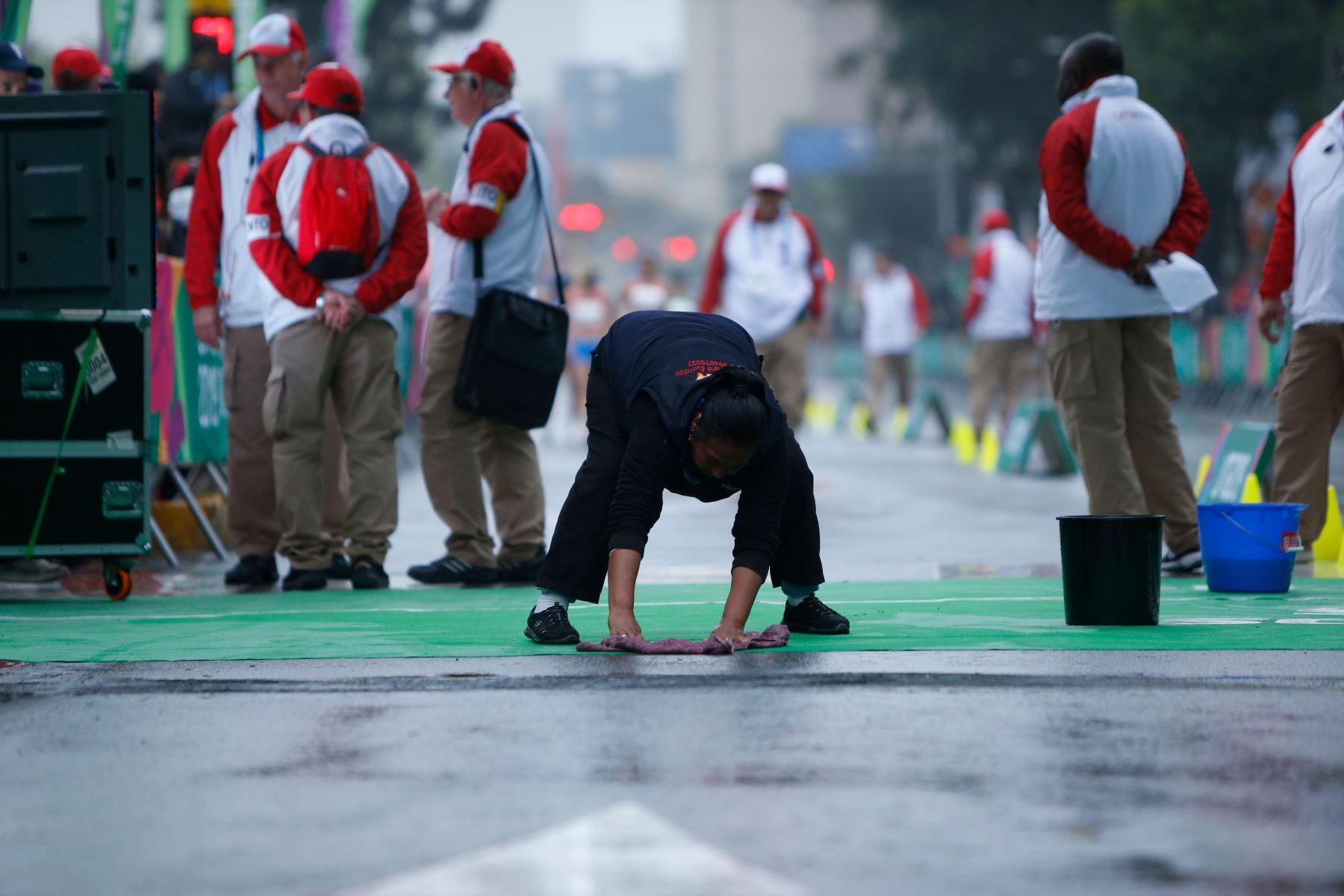 Trabajadora limpiando la pista de partida de la competencia de atletismo de marcha 20 km mujeres. Lugar: Parque Kennedy Miraflores. Foto: ANDINA/ Lima 2019