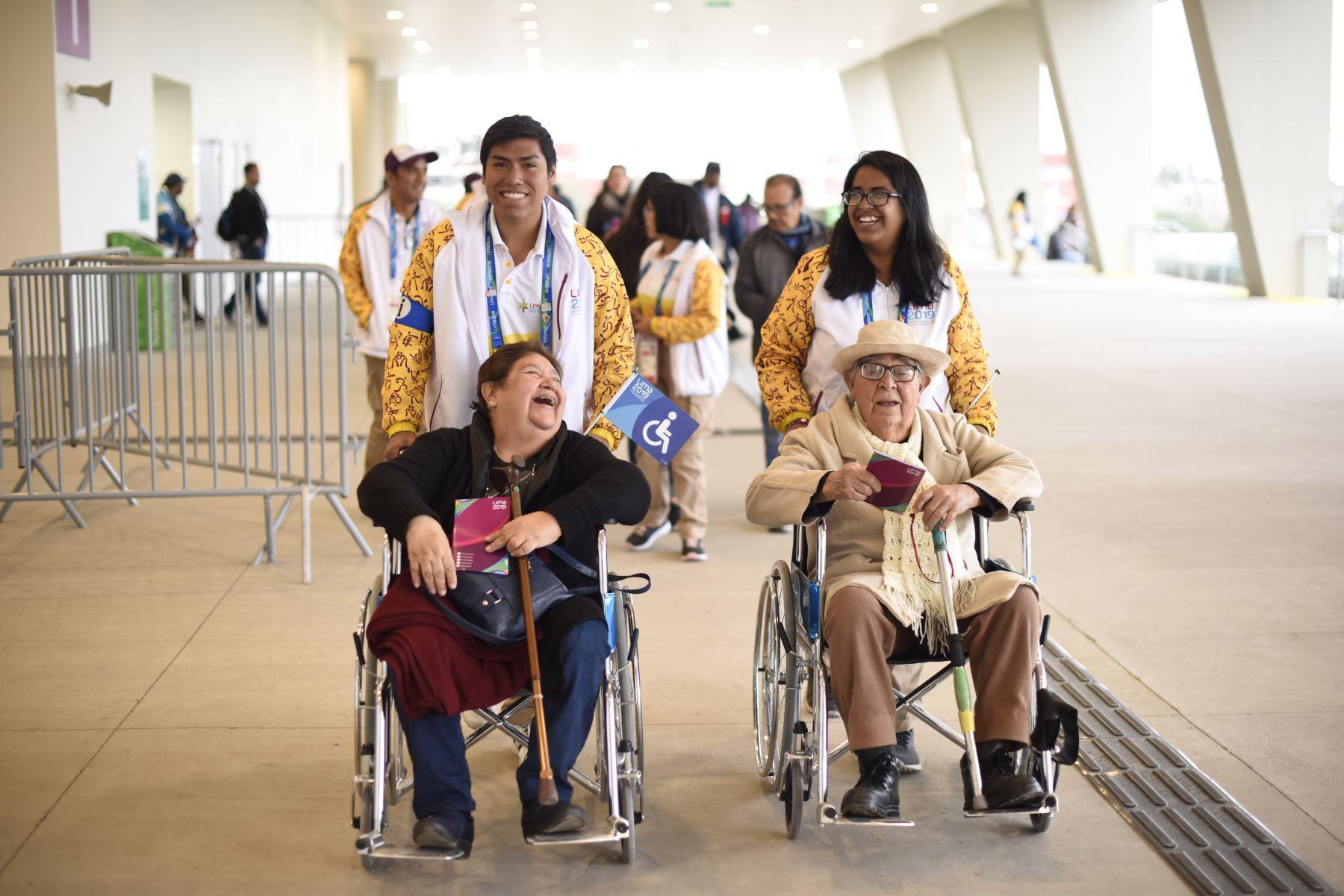 Voluntarios de Lima 2019 llevan a  una pareja de ancianos con silla de ruedas a las tribunas de la  villa atlética de la Videna. Foto: ANDINA/ Lima 2019
